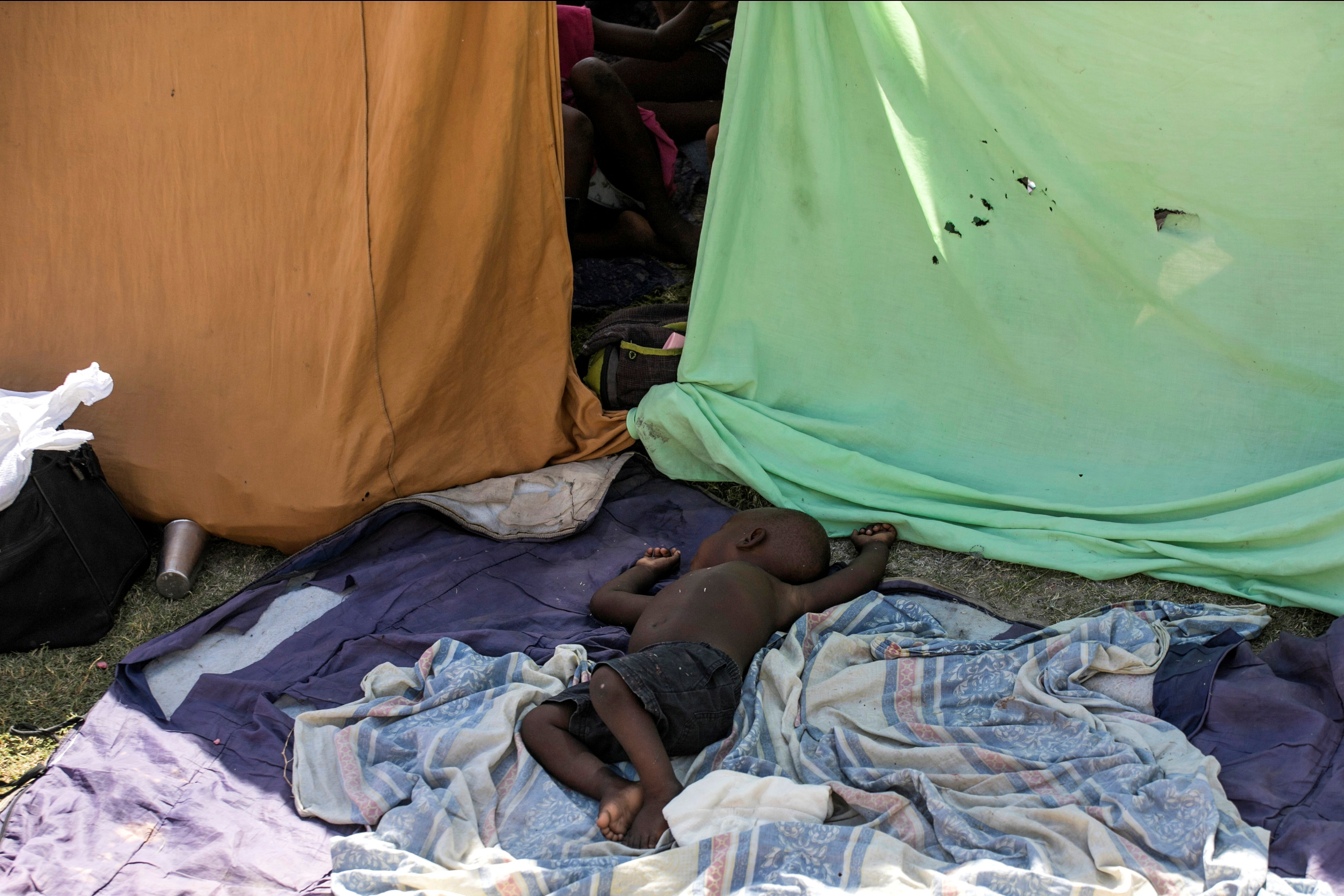 A child lies on blankets at an encampment set up on a soccer field after Saturday's 7.2 magnitude quake, in Les Cayes, Haiti August 16, 2021. REUTERS/Ralph Tedy Erol