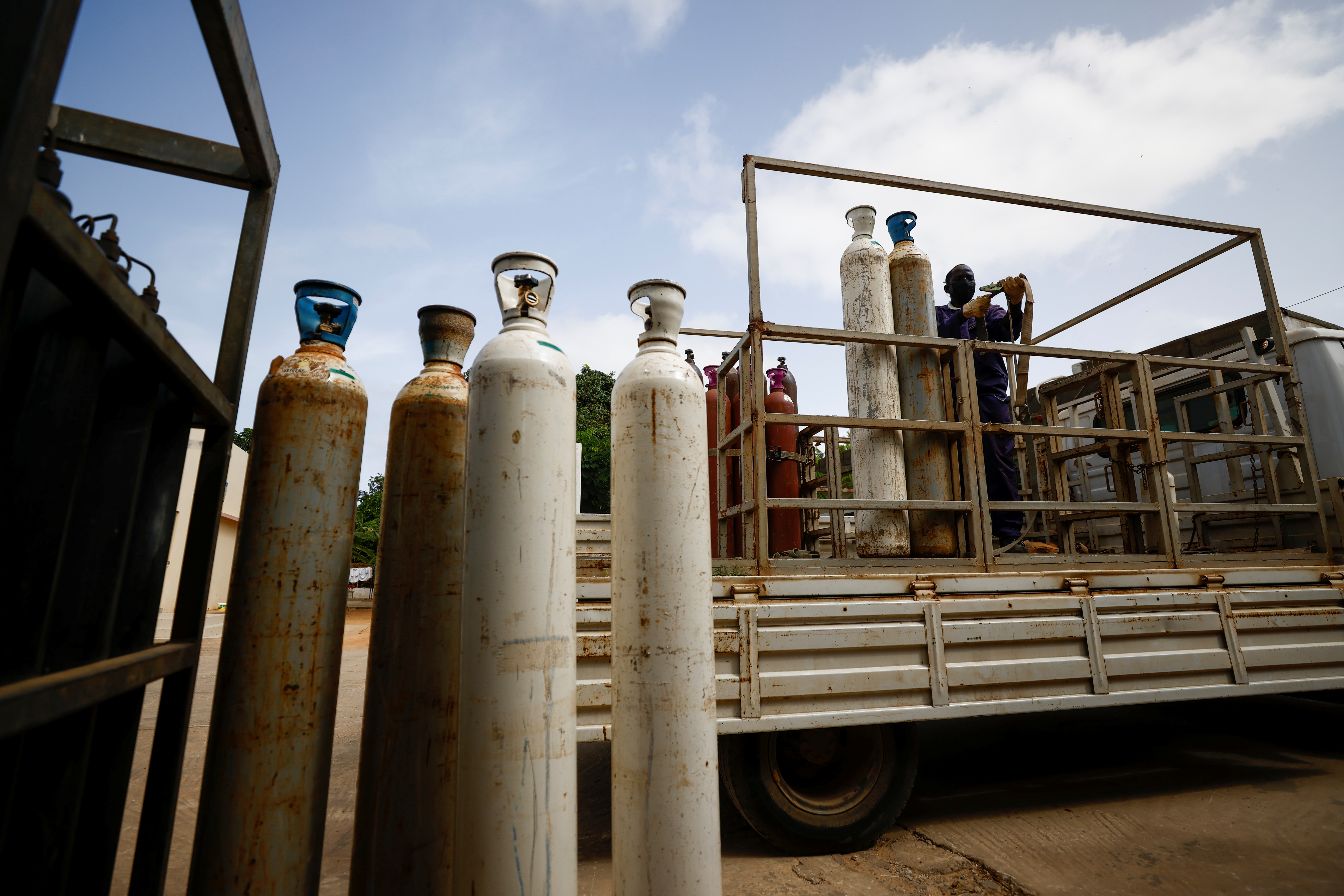 Babacar Gueye, 56, a worker of Molecules gas company prepares to offload oxygen cylinders outside the infectious diseases department of the Fann University Hospital in Dakar, amid a surge of coronavirus disease (COVID-19) cases in Senegal July 28, 2021. Picture taken July 28, 2021. REUTERS/Zohra Bensemra