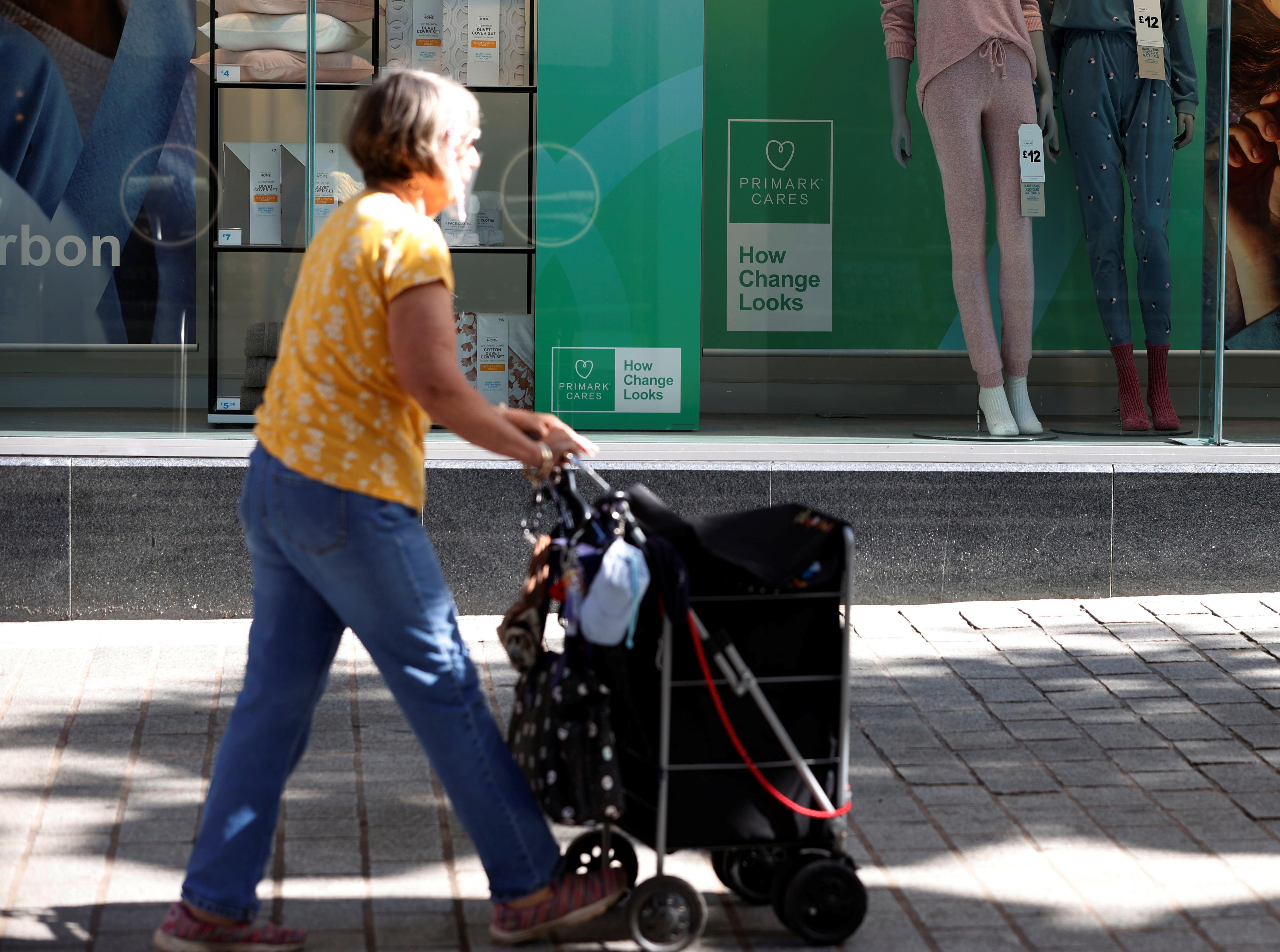 A woman walks past a window display showing new environmentally themed posters at a Primark store in Liverpool, Britain, September 15, 2021. REUTERS/Phil Noble