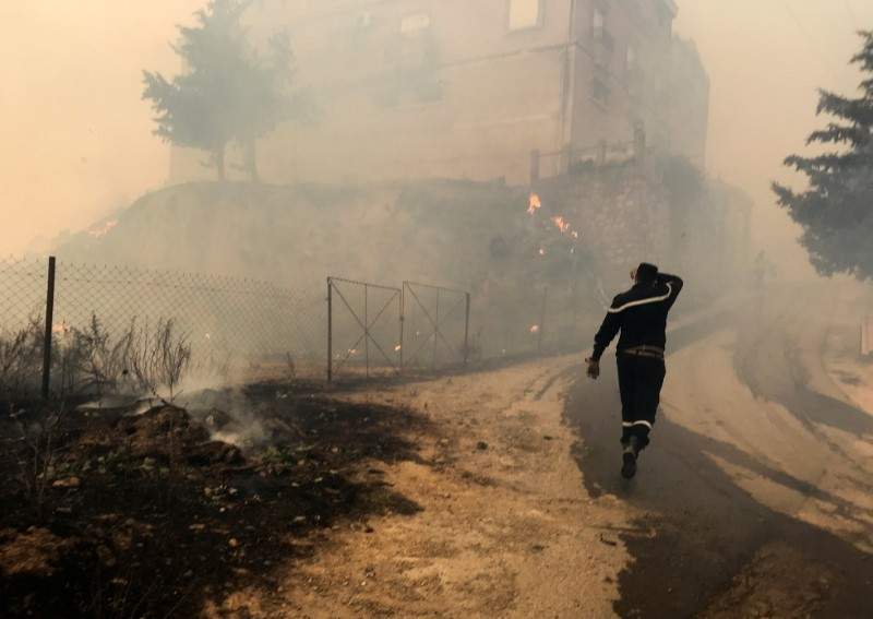 A civil protection rescue worker walks near smoke rising from a forest fire in the mountainous Tizi Ouzou province, east of Algiers, Algeria August 10, 2021. REUTERS/Abdelaziz Boumzar