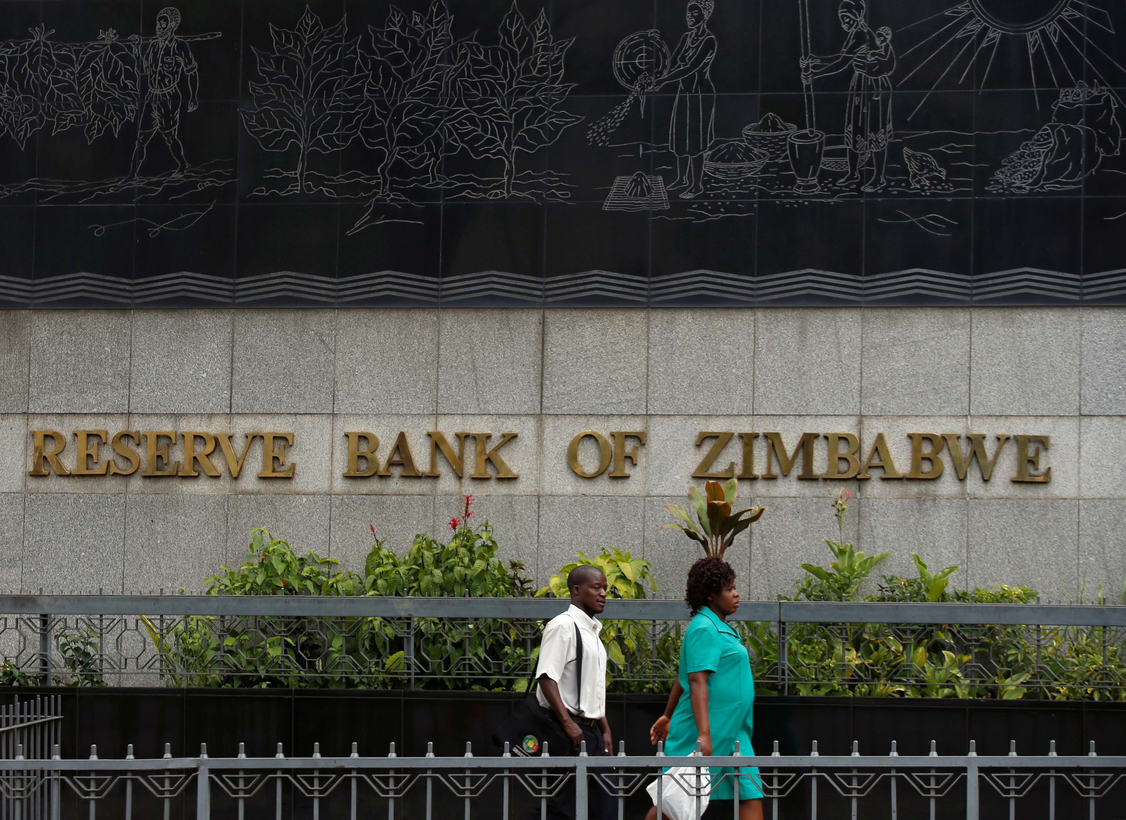 People walk past the Reserve Bank of Zimbabwe building in Harare, Zimbabwe, February 25, 2019. REUTERS/Philimon Bulawayo