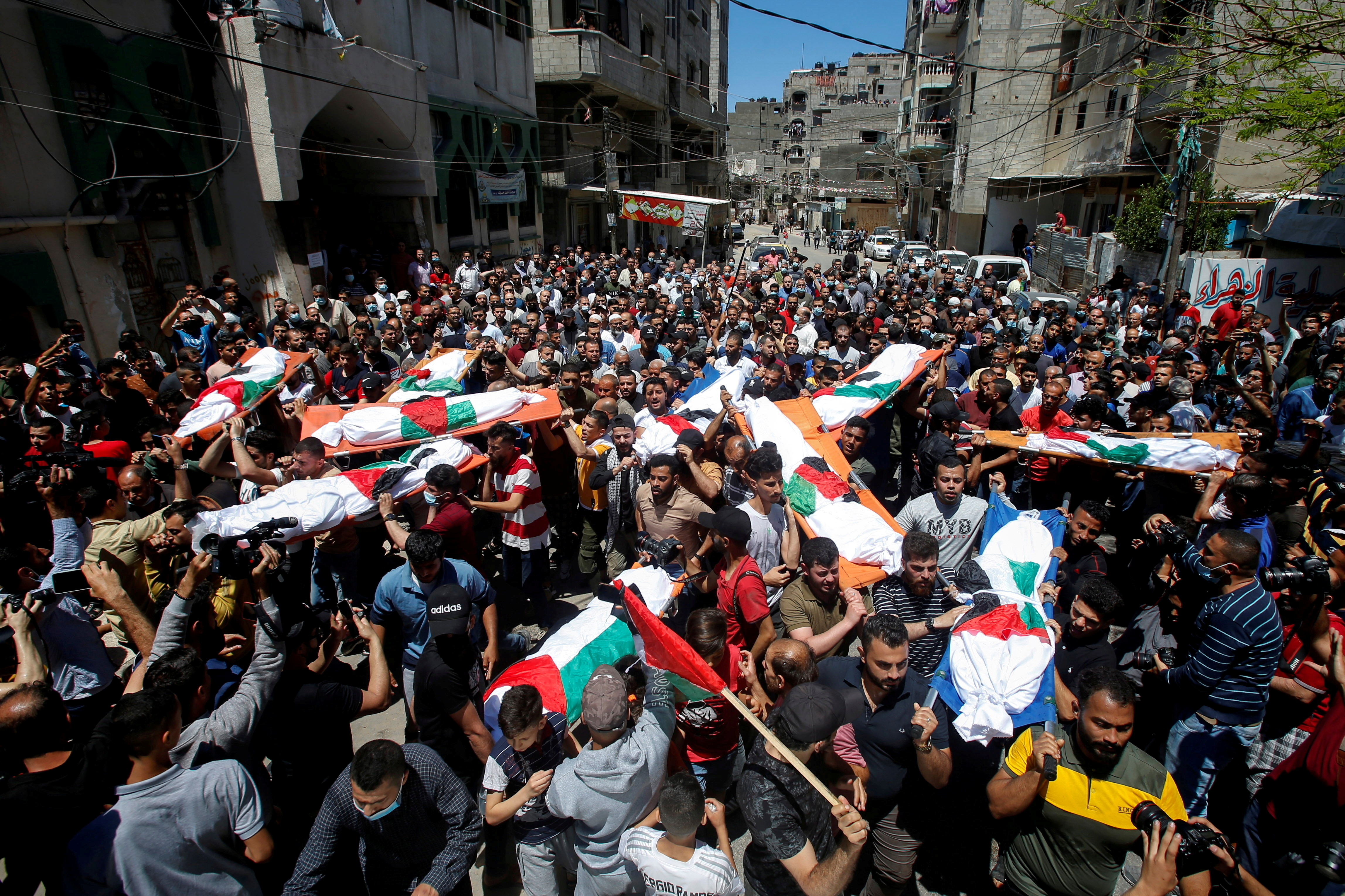 Mourners carry the bodies of Palestinians, including members of Abu Hatab family, who were killed amid a flare-up of Israeli-Palestinian violence, during their funeral at the Beach refugee camp, in Gaza City May 15, 2021. REUTERS/Mohammed Salem