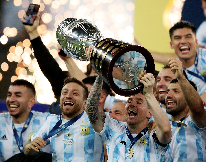 Soccer Football - Copa America  2021 - Final - Brazil v Argentina - Estadio Maracana, Rio de Janeiro, Brazil - July 10, 2021 Argentina's Lionel Messi and teammates celebrate winning the Copa America with the trophy REUTERS/Ricardo Moraes