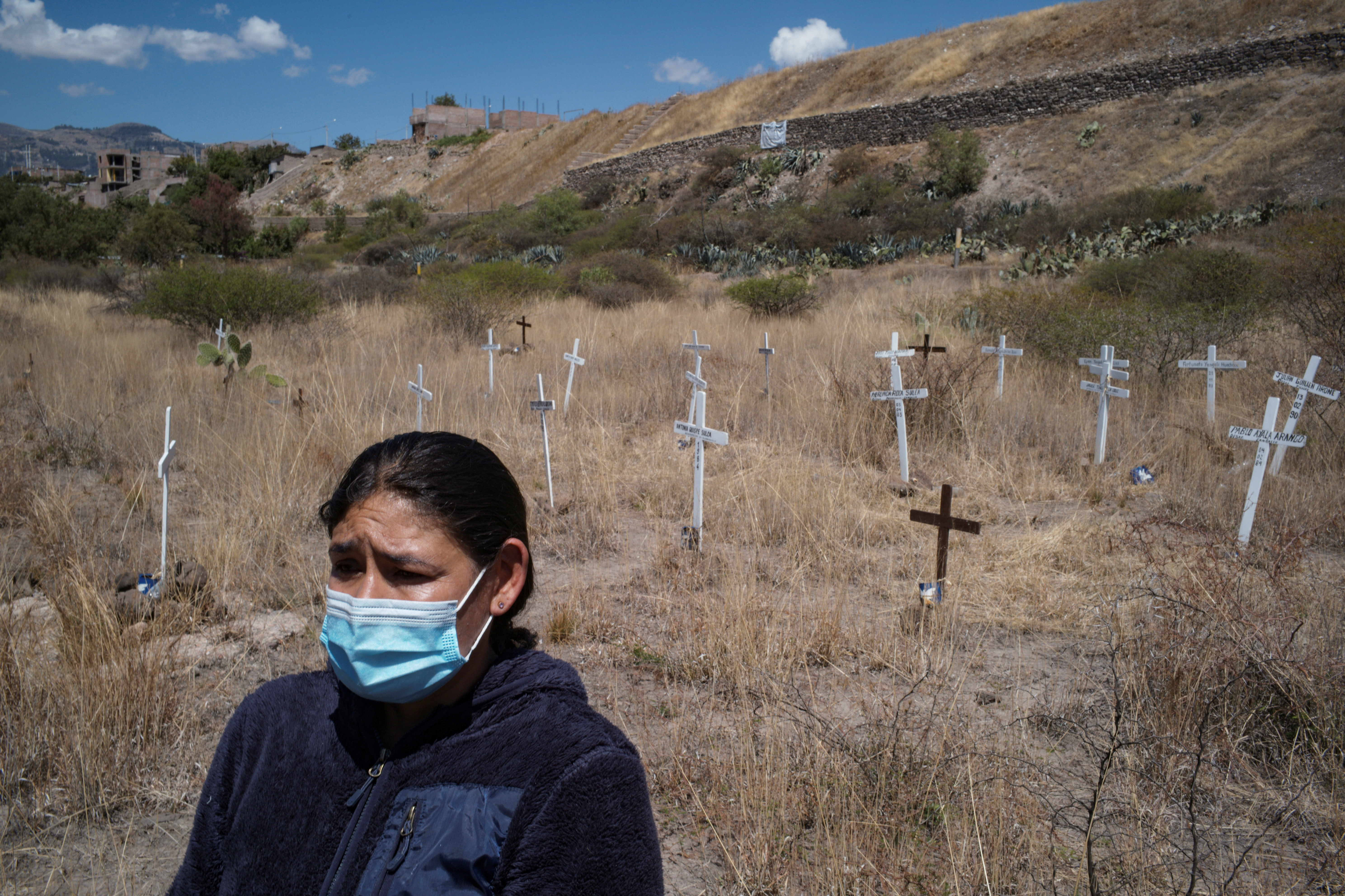 A caretaker stands in front of crosses for people who disappeared during the era of Shining Path, the Peruvian guerrilla group whose founder Abimael Guzman recently died, at the memorial site La Hoyada, in Ayacucho, Peru September 14, 2021. REUTERS/Alessandro Cinque