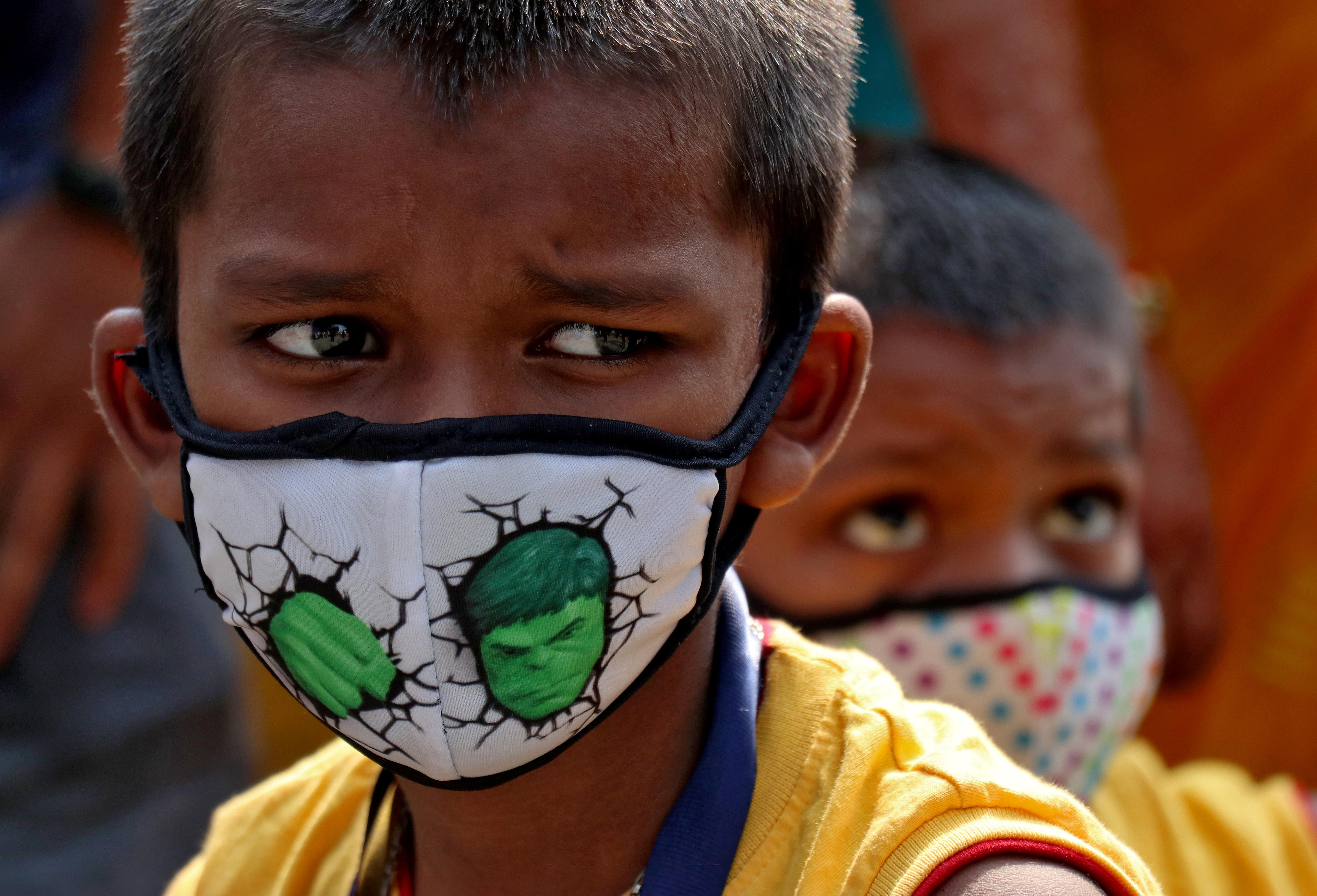 Children wearing protective masks wait to enter the Lokmanya Tilak Terminus railway station, amidst the spread of the coronavirus disease (COVID-19) in Mumbai, India, April 14, 2021. REUTERS/Niharika Kulkarni