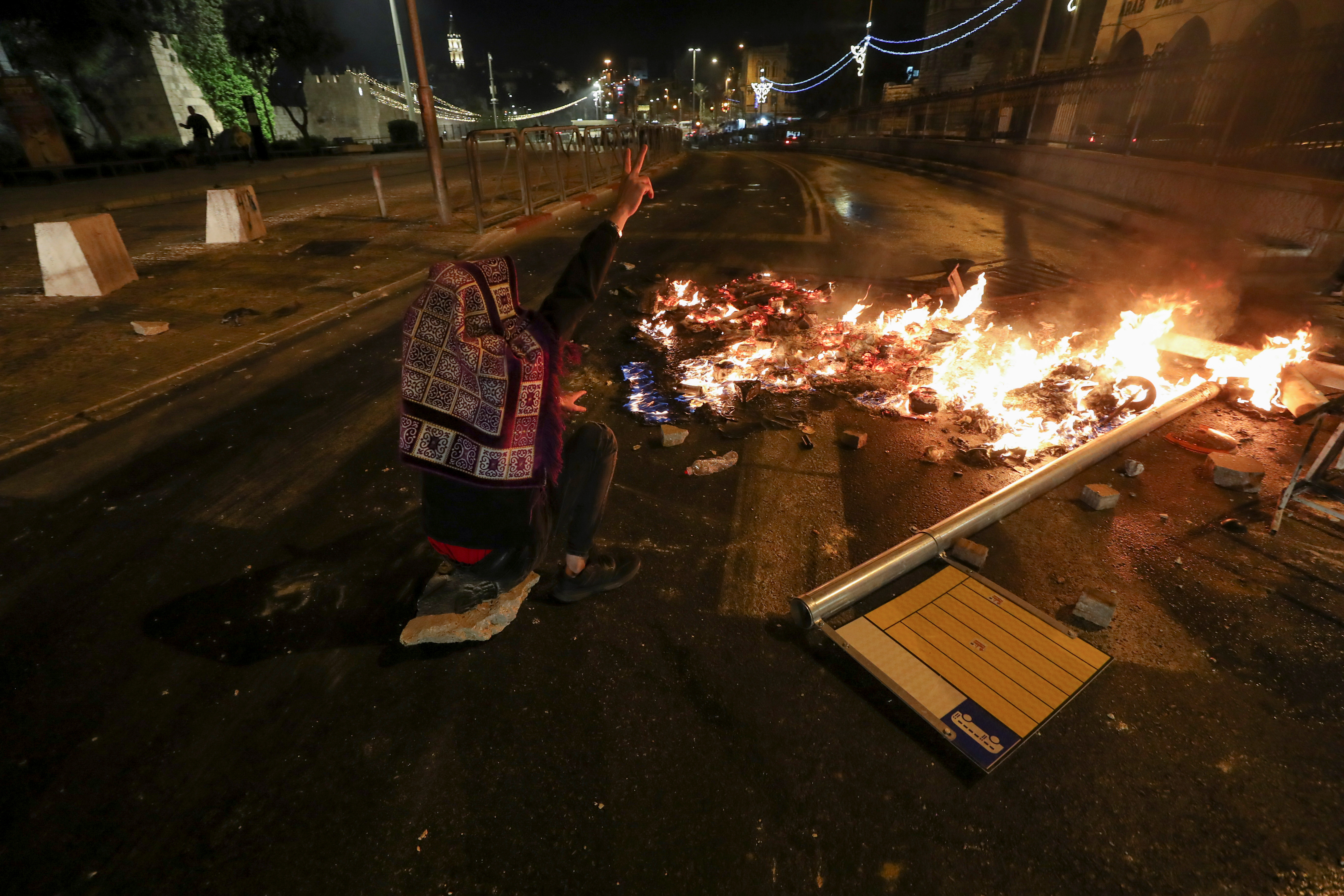 A Palestinian sitting next to a burning barricade flashes a ''V'' sign during clashes with Israeli police, as the Muslim holy fasting month of Ramadan continues, in Jerusalem, April 22, 2021. REUTERS/Ammar Awad