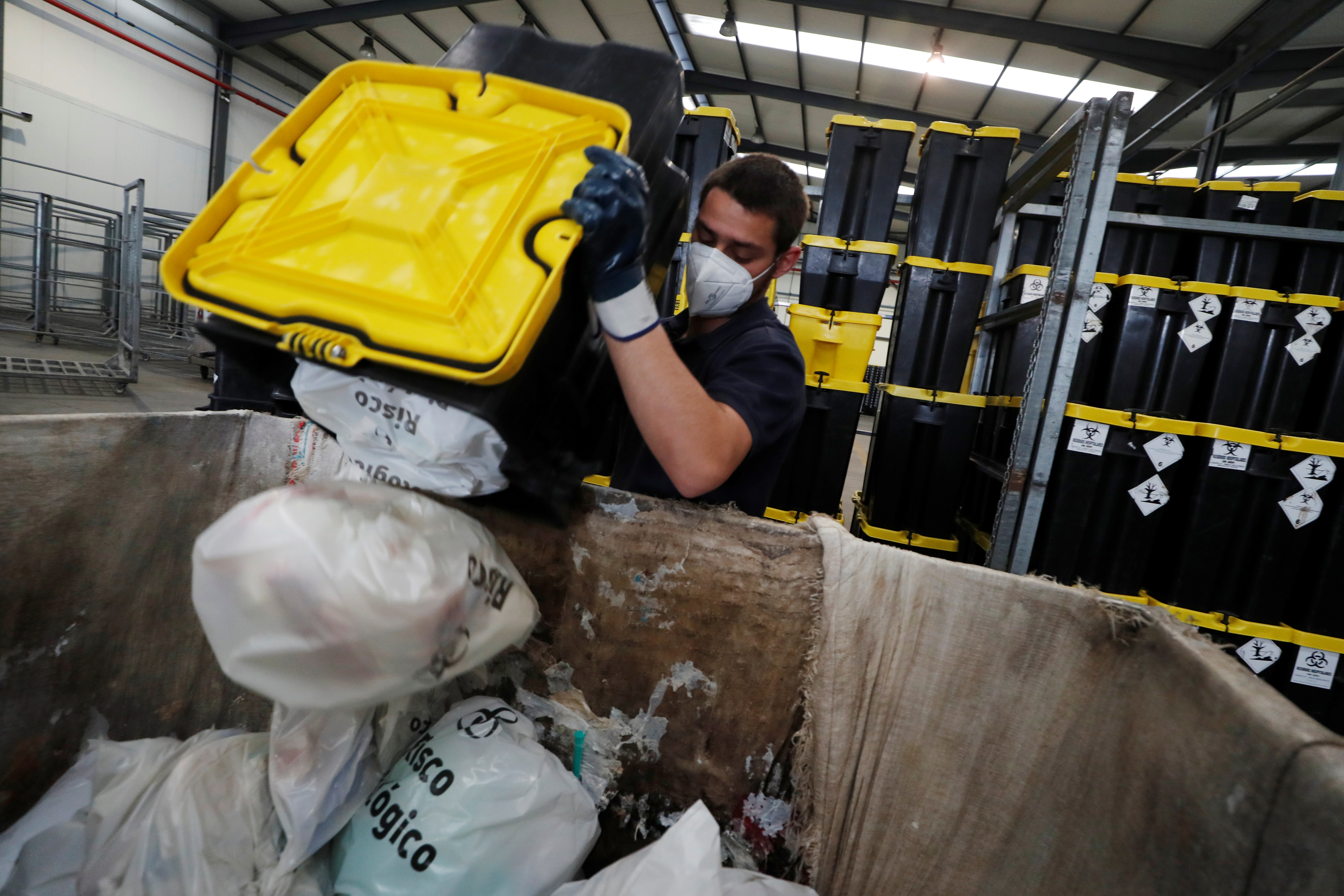 A worker removes used supplies from COVID-19 vaccines and protective equipment from a container in a waste treatment facility, amid the coronavirus disease (COVID-19) pandemic, in Chamusca, Santarem, Portugal, April 21, 2021.  REUTERS/Pedro Nunes