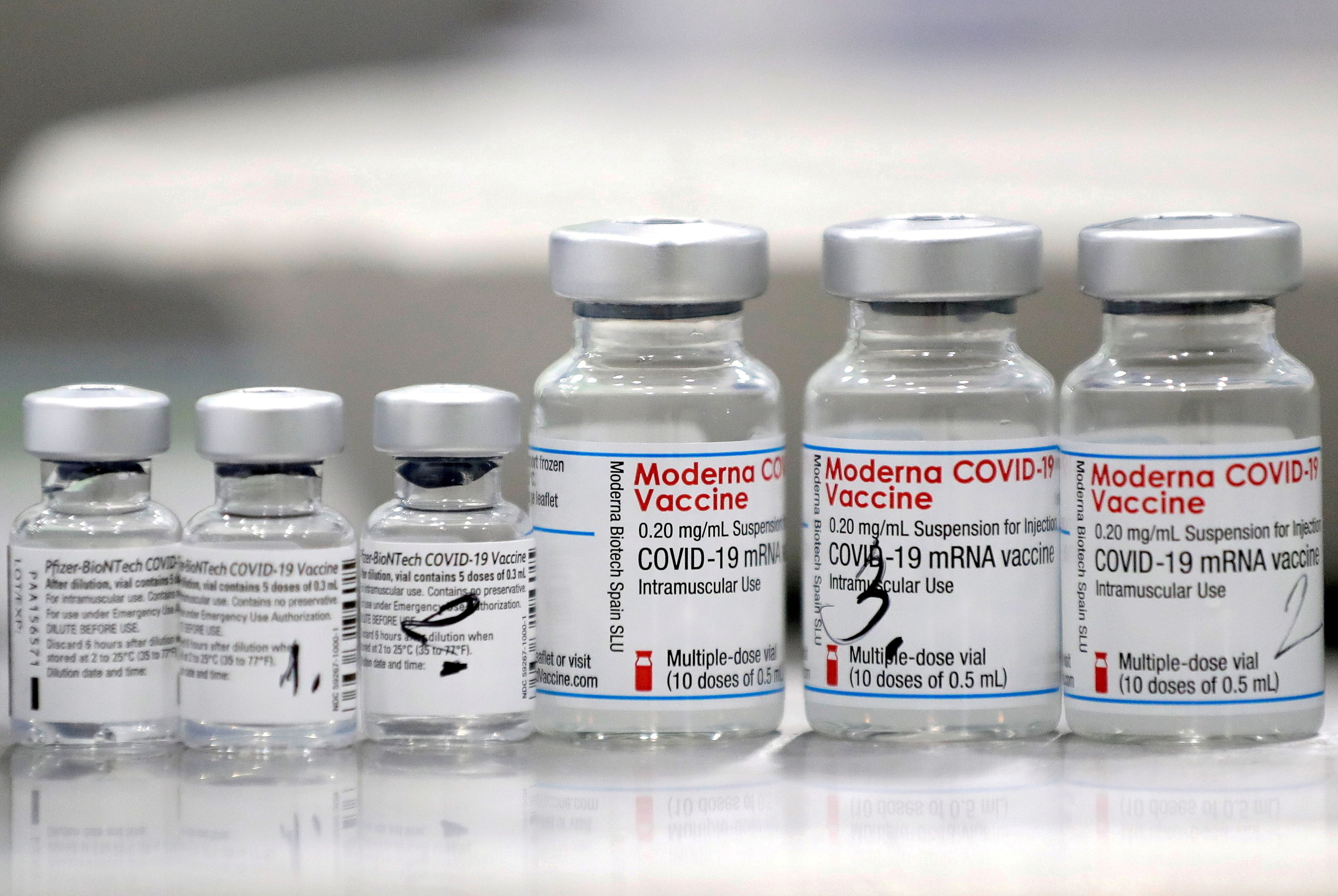 FILE PHOTO: Vials of coronavirus disease (COVID-19) vaccines of Pfizer-BioNTech and Moderna are seen in the town of Ricany near Prague, Czech Republic, February 25, 2021.  REUTERS/David W Cerny/File Photo/File Photo/File Photo