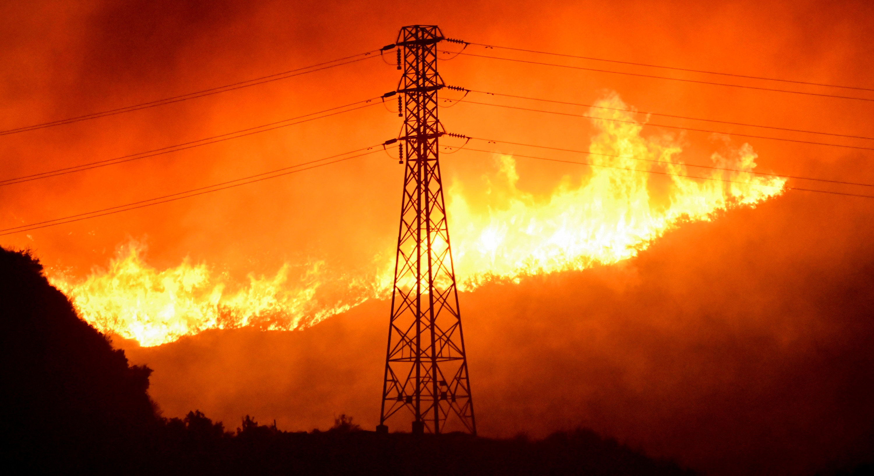A wind-driven wildfire burns near power line tower in Sylmar, California, U.S., October 10, 2019.  REUTERS/Gene Blevins/File Photo