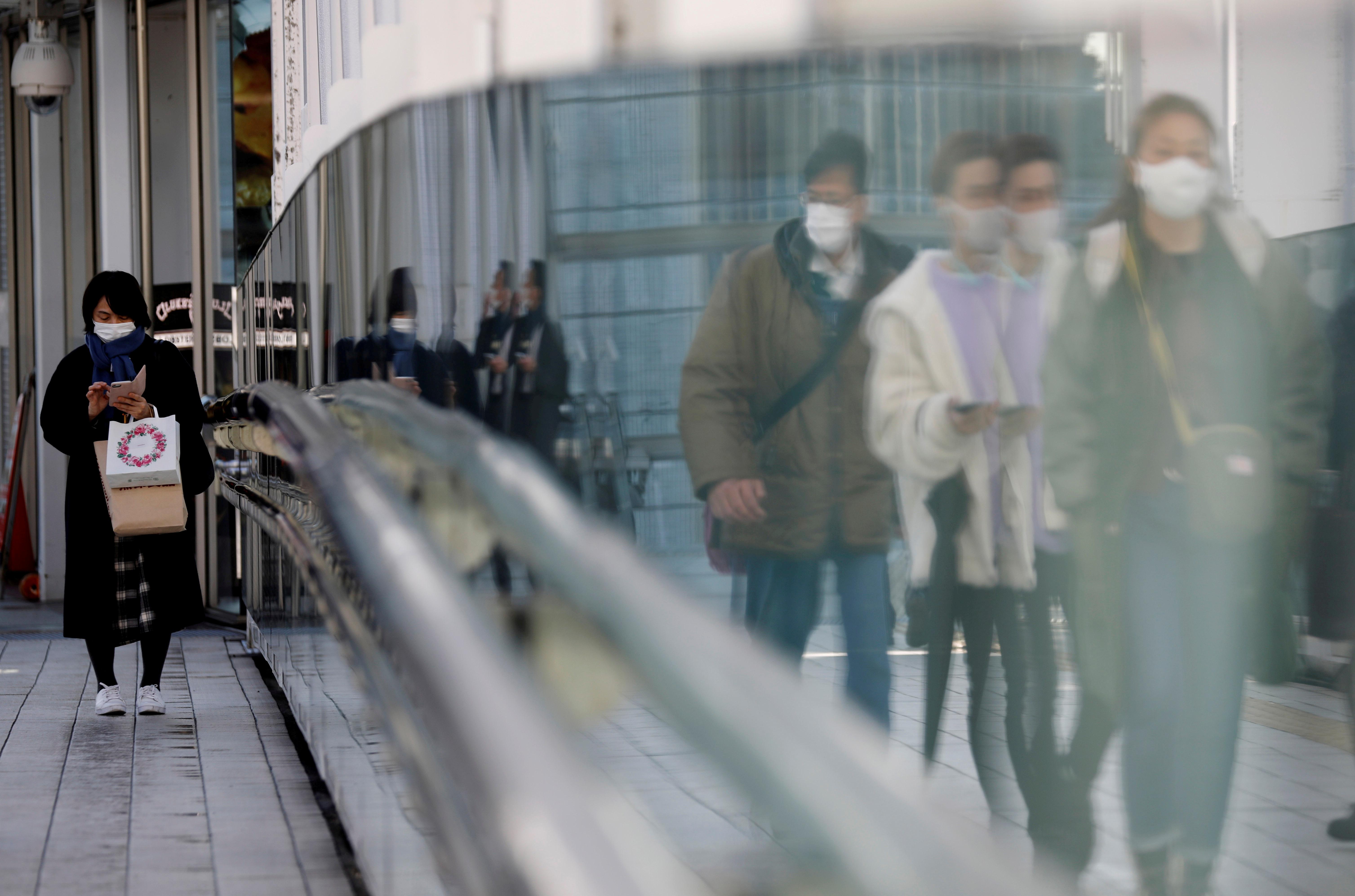 Pedestrians wearing protective masks amid the coronavirus disease (COVID-19) outbreak, walk on a street in Tokyo, Japan, February 2, 2021. REUTERS/Kim Kyung-Hoon/File Photo