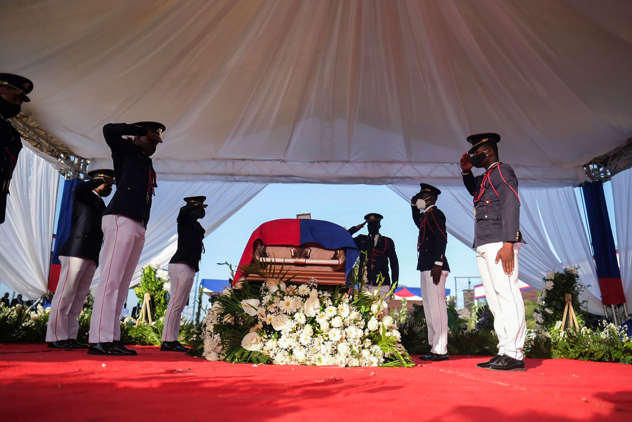 Pallbearers in military attire salute next to a coffin holding the body of late Haitian President Jovenel Moise after he was shot dead at his home in Port-au-Prince earlier this month, in Cap-Haitien, July 23, 2021. REUTERS/Ricardo Arduengo
