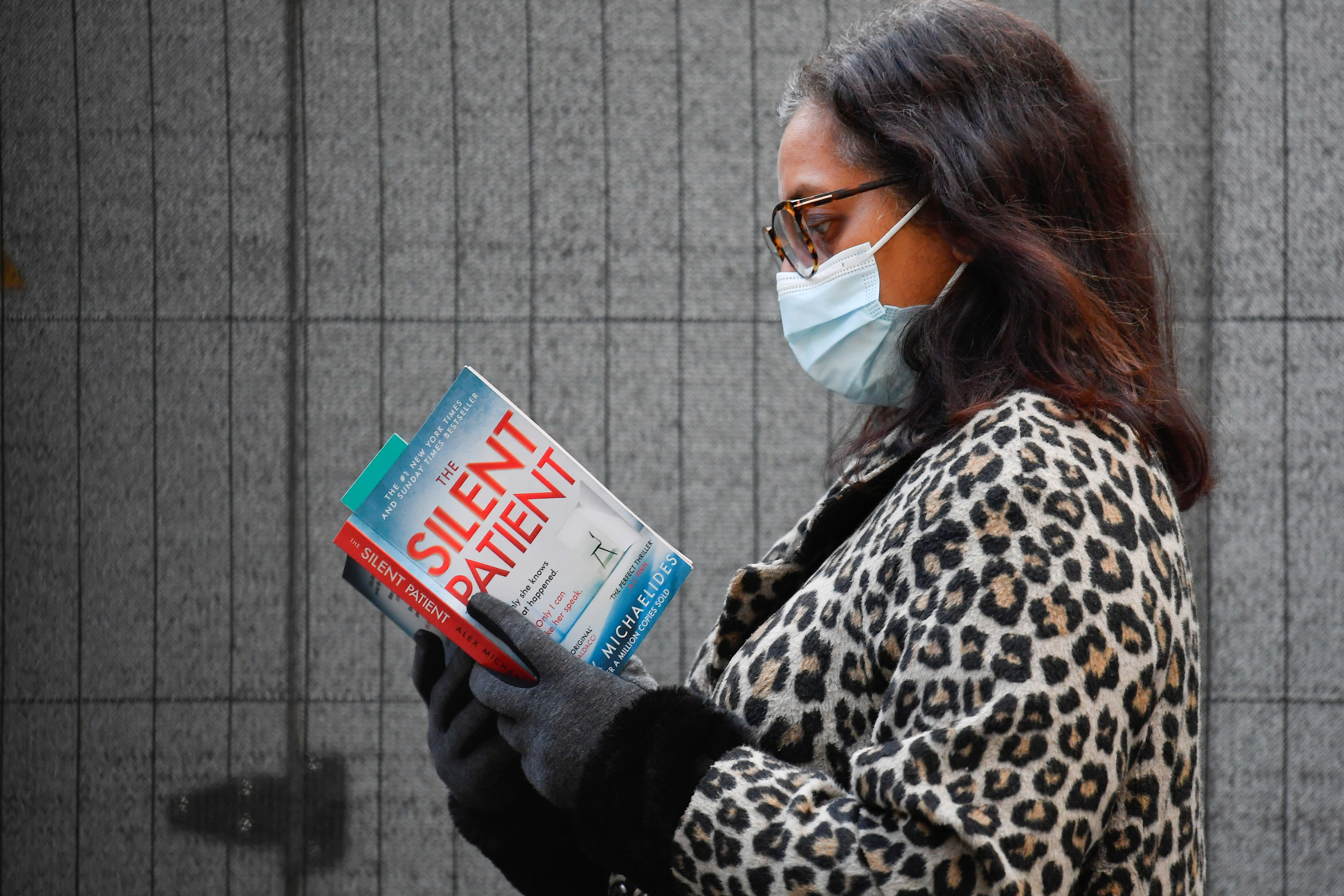 A woman reads as she waits to receive a COVID-19 vaccine at London Bridge vaccination centre, amidst the spread of the coronavirus disease (COVID-19), in London, Britain December 30, 2020. REUTERS/Toby Melville
