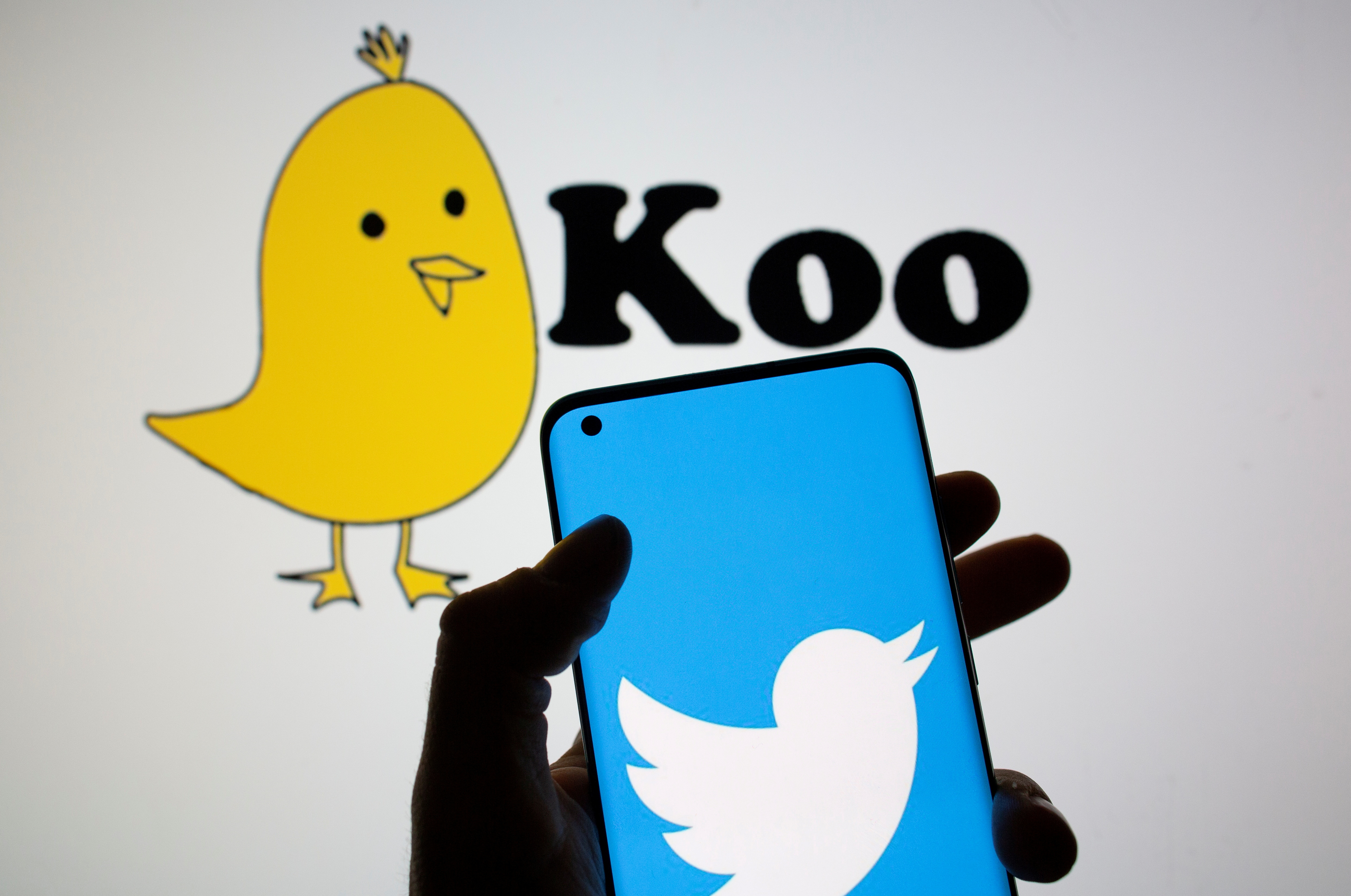 Twitter logo is seen on smartphone in front of displayed Koo app logo in this illustration taken, February 10, 2021. REUTERS/Dado Ruvic/Illustration/File Photo