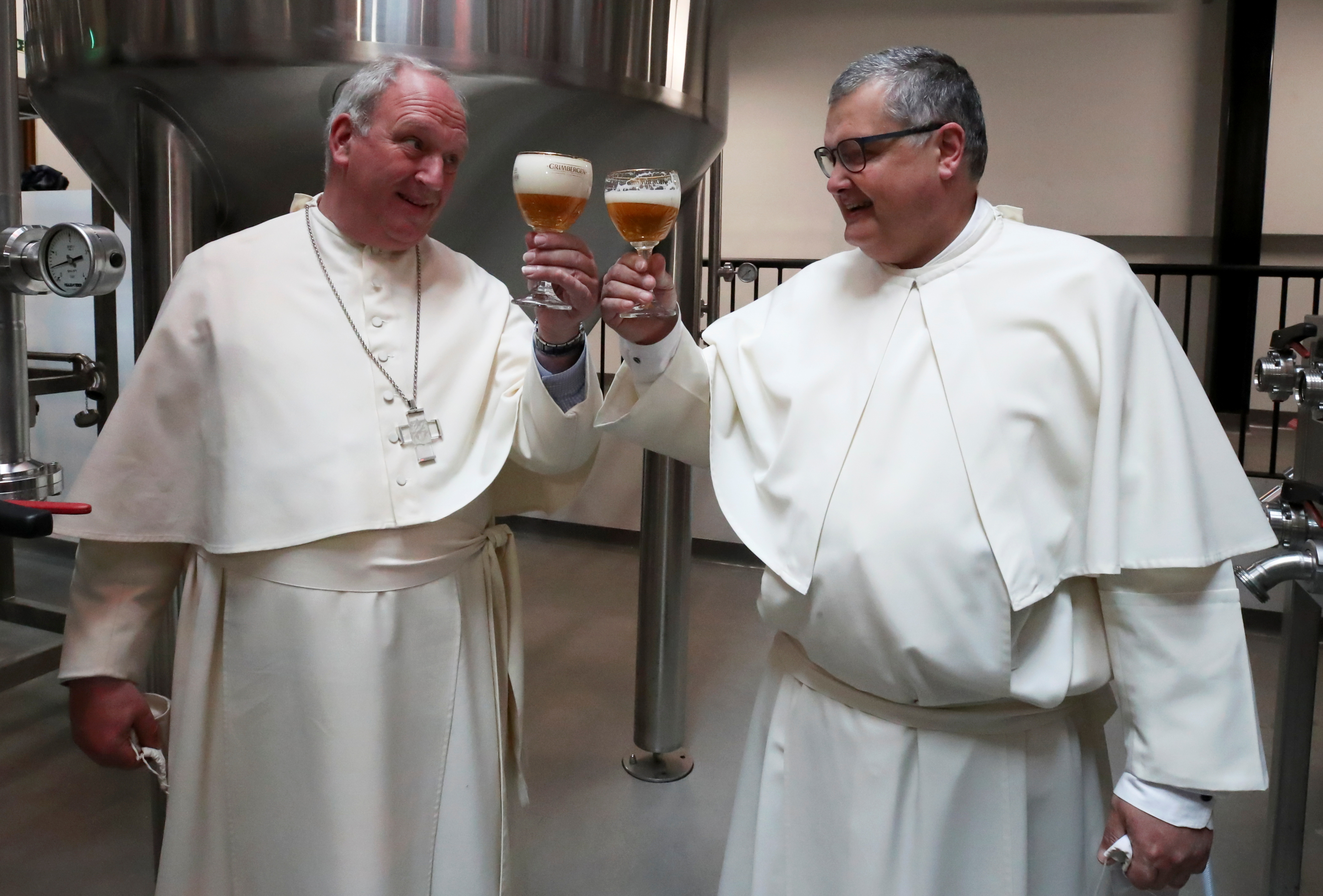 Father Karel Stautemas and abbot Erik toast after blessing beer tanks at the Belgian Abbey of Grimbergen, which returns to brewing after a break of more than 200 years with a new microbrewery in Grimbergen, Belgium May 26, 2021. Picture taken May 26, 2021. REUTERS/Yves Herman