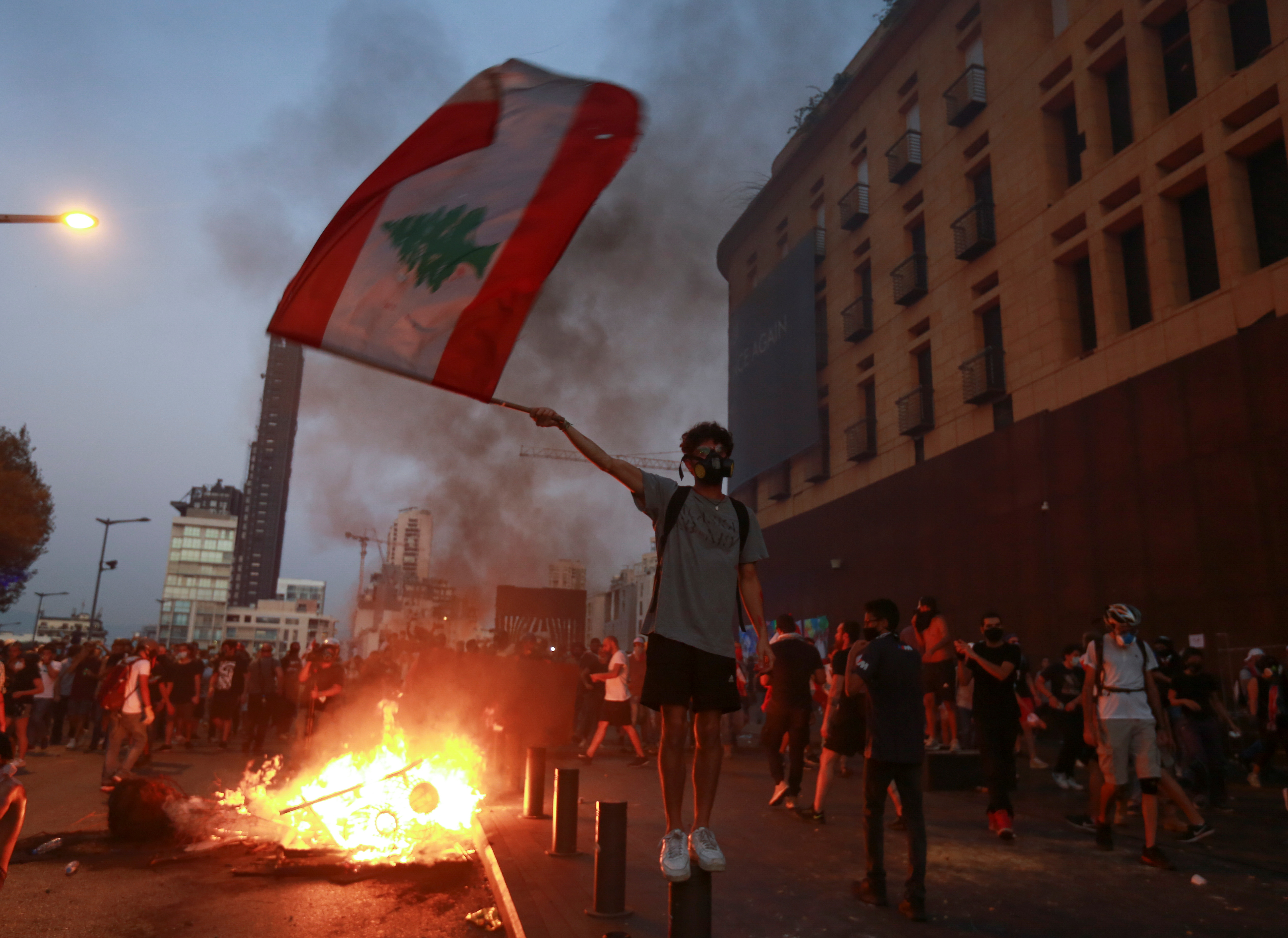 A demonstrator holds the Lebanese flag during a protest near parliament, as Lebanon marks the one-year anniversary of the explosion in Beirut, Lebanon August 4, 2021. REUTERS/Aziz Taher
