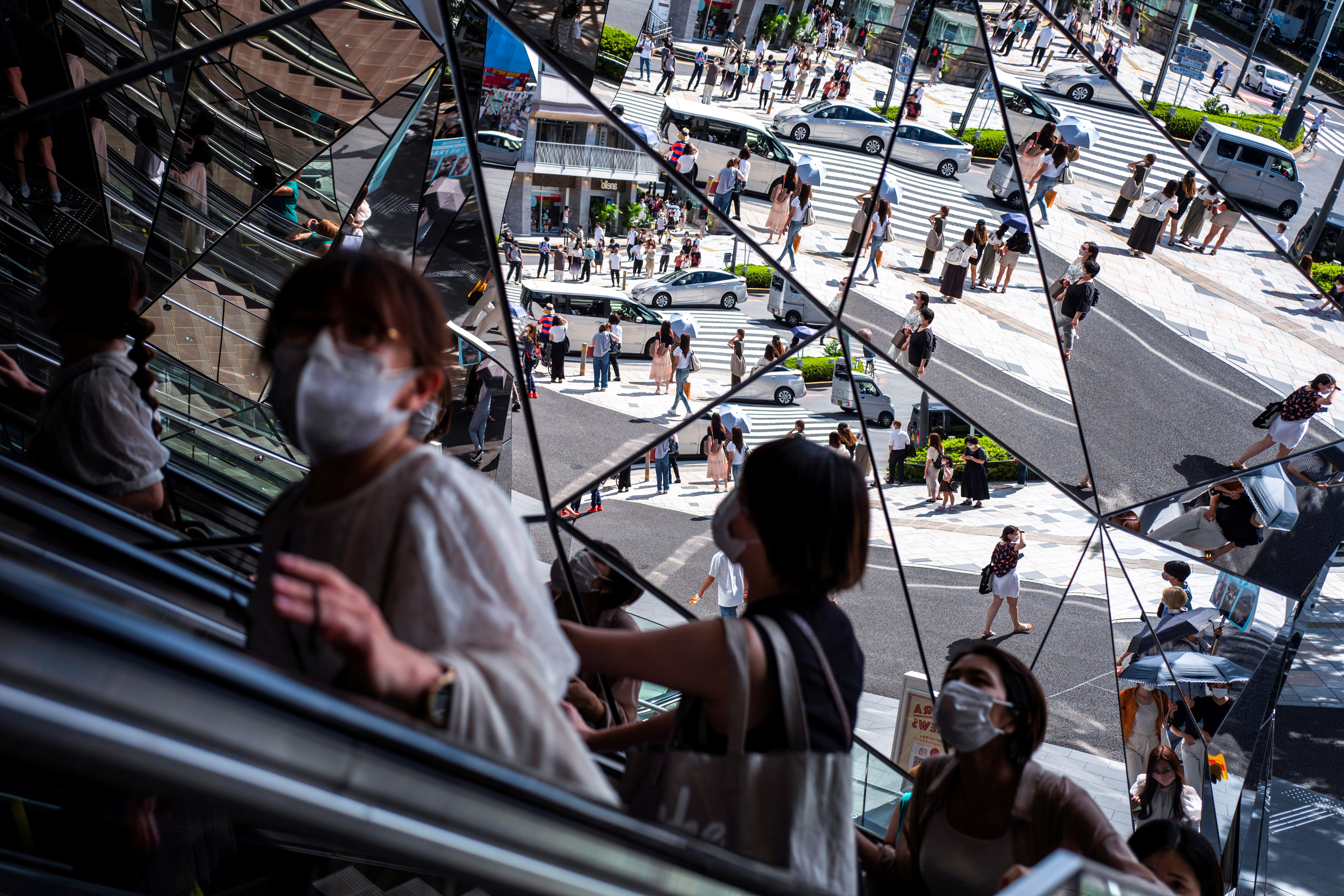 People wearing protective masks are reflected in the mirror at a shopping mall in Tokyo amid the coronavirus disease (COVID-19) outbreak in Tokyo, Japan, August 19, 2021. REUTERS/Athit Perawongmetha/File Photo