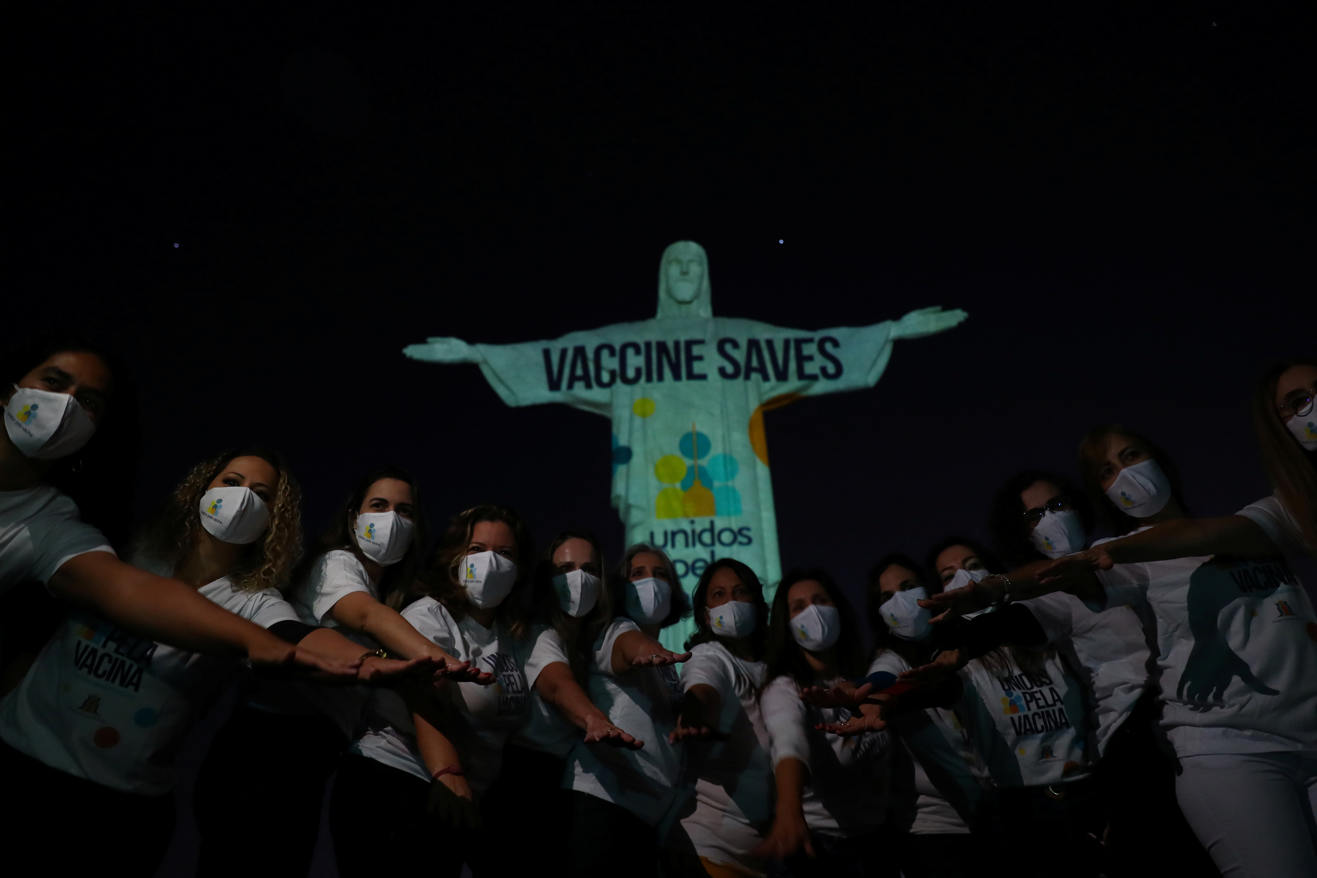 Members of the United Vaccine Movement pose in front of the Christ the Redeemer statue as the message