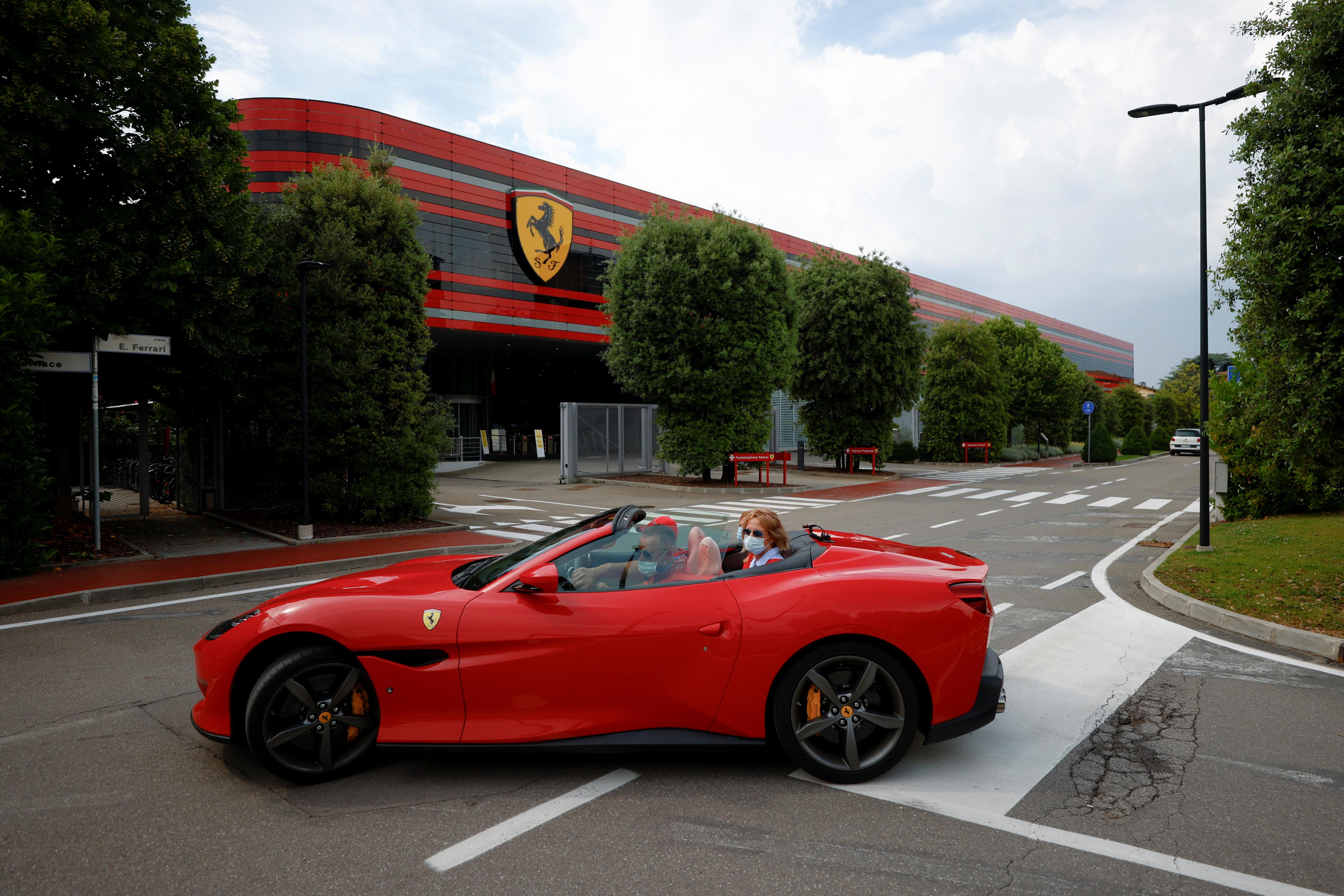 A man drives a Ferrari past the company's headquarters in Maranello, Italy, June 8, 2021. Picture taken June 8, 2021. REUTERS/Guglielmo Mangiapane