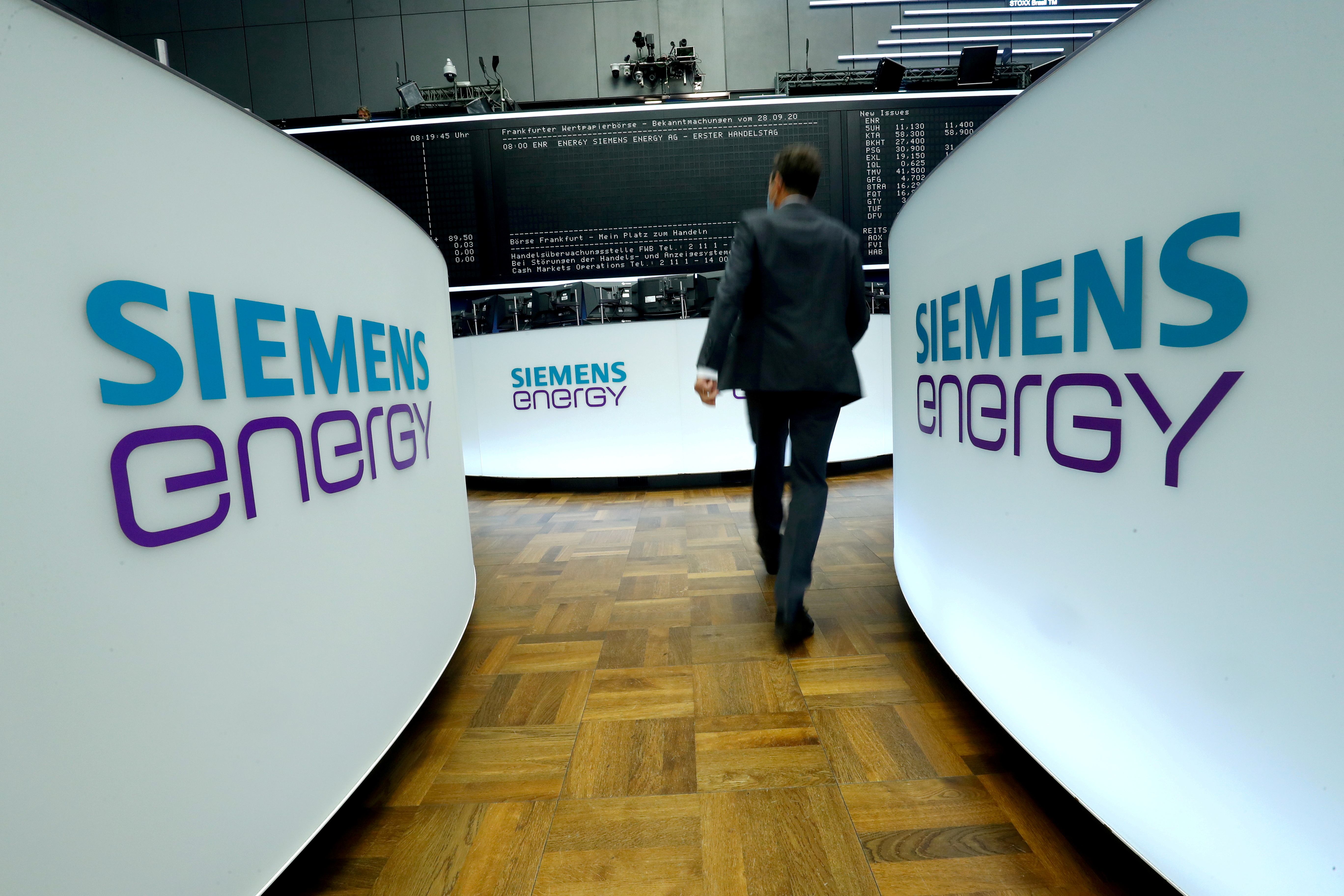 A trader walks next to Siemens Energy AG logos during Siemens Energy's initial public offering (IPO) at the Frankfurt Stock Exchange in Frankfurt, Germany, September 28, 2020.  REUTERS/Ralph Orlowski/File Photo