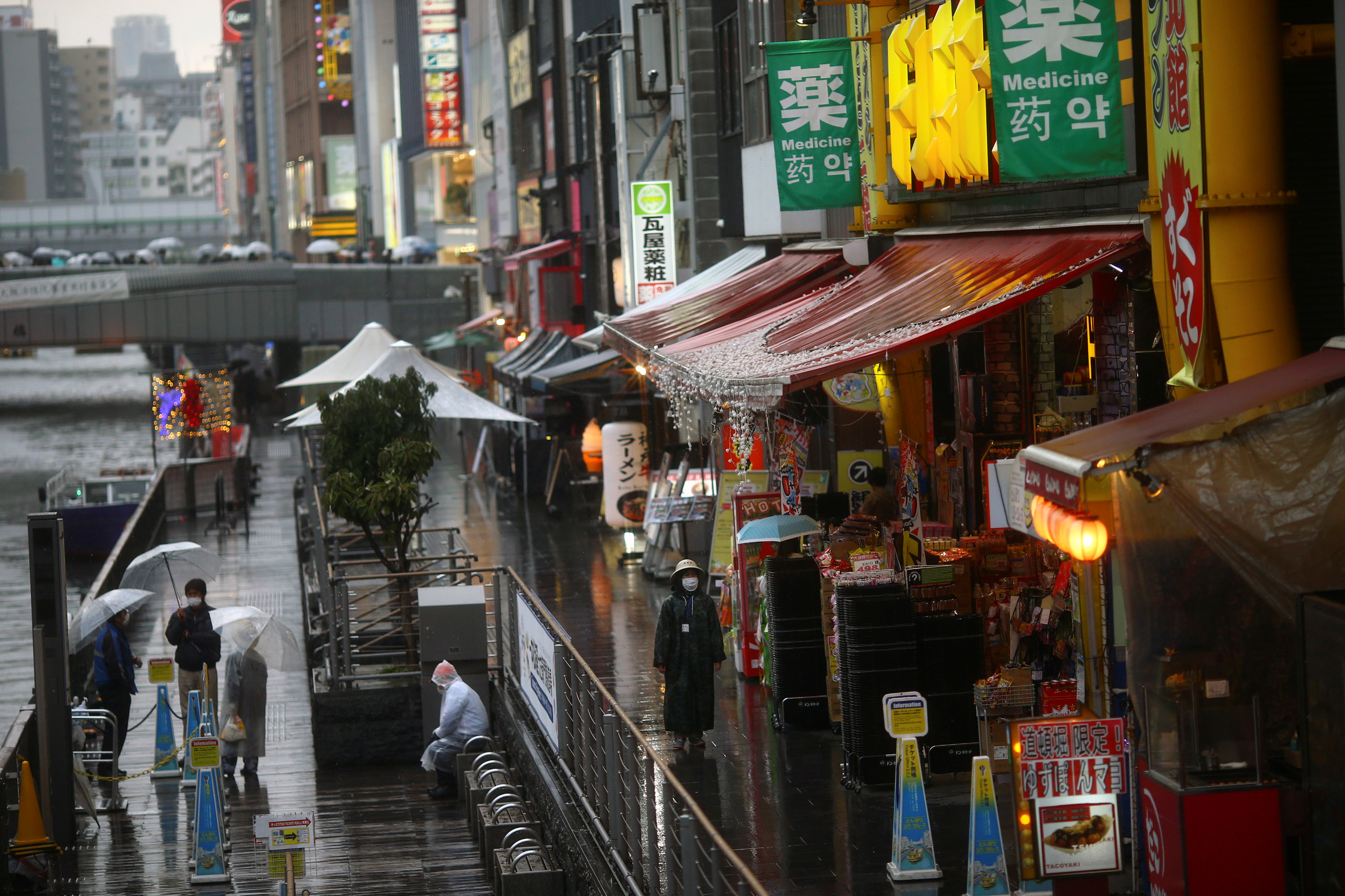 A woman, wearing protective mask following an outbreak of the coronavirus disease (COVID-19), walks on an almost empty street in the Dotonbori entertainment district of Osaka, Japan, March 14, 2020.   REUTERS/Edgard Garrido