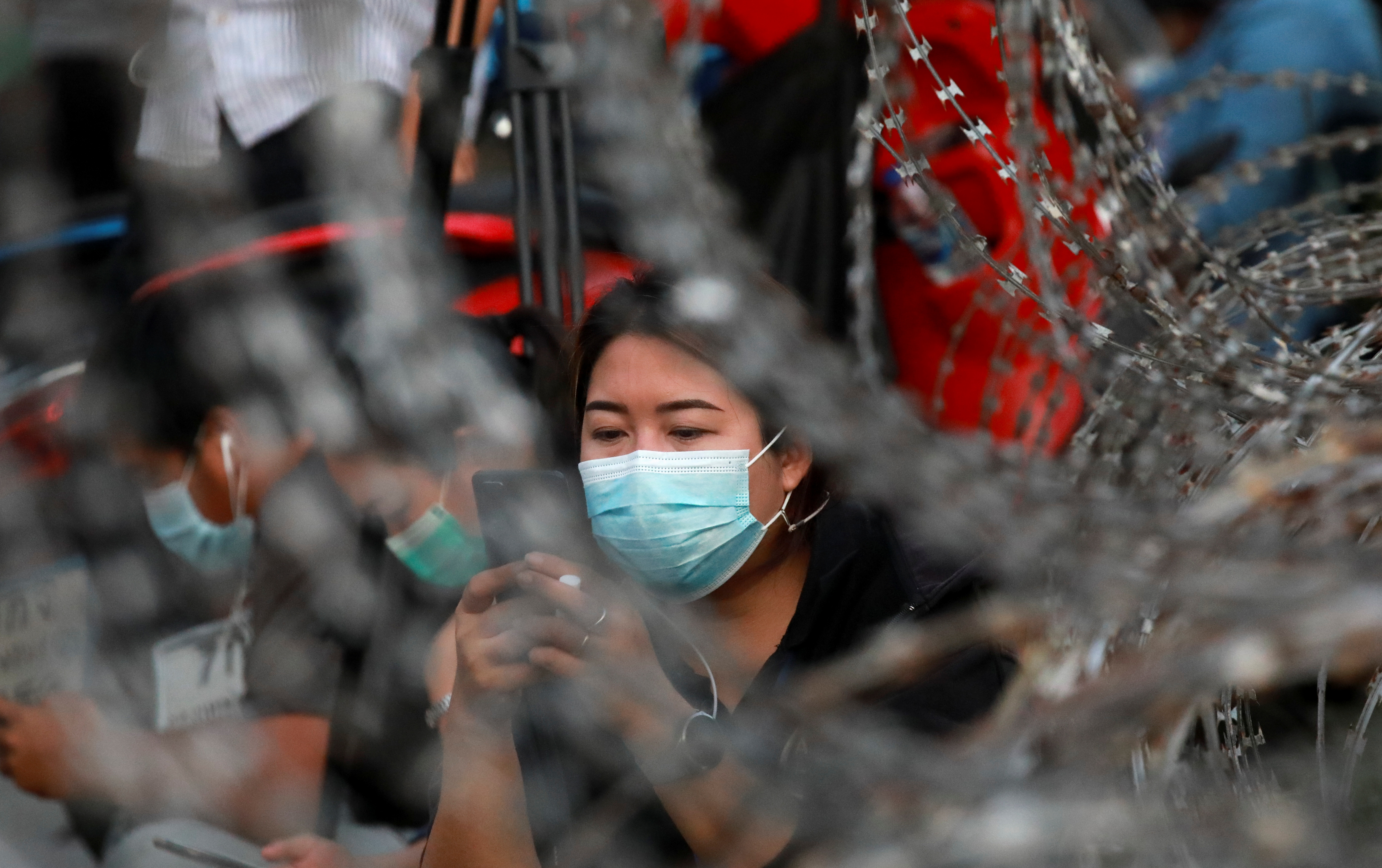A supporter of anti-government protest leaders arrested and charged with lese majeste looks at her phone while waiting for their release on bail outside Klongprem Central Prisonin Bangkok, Thailand May 11, 2021. REUTERS/Soe Zeya Tun
