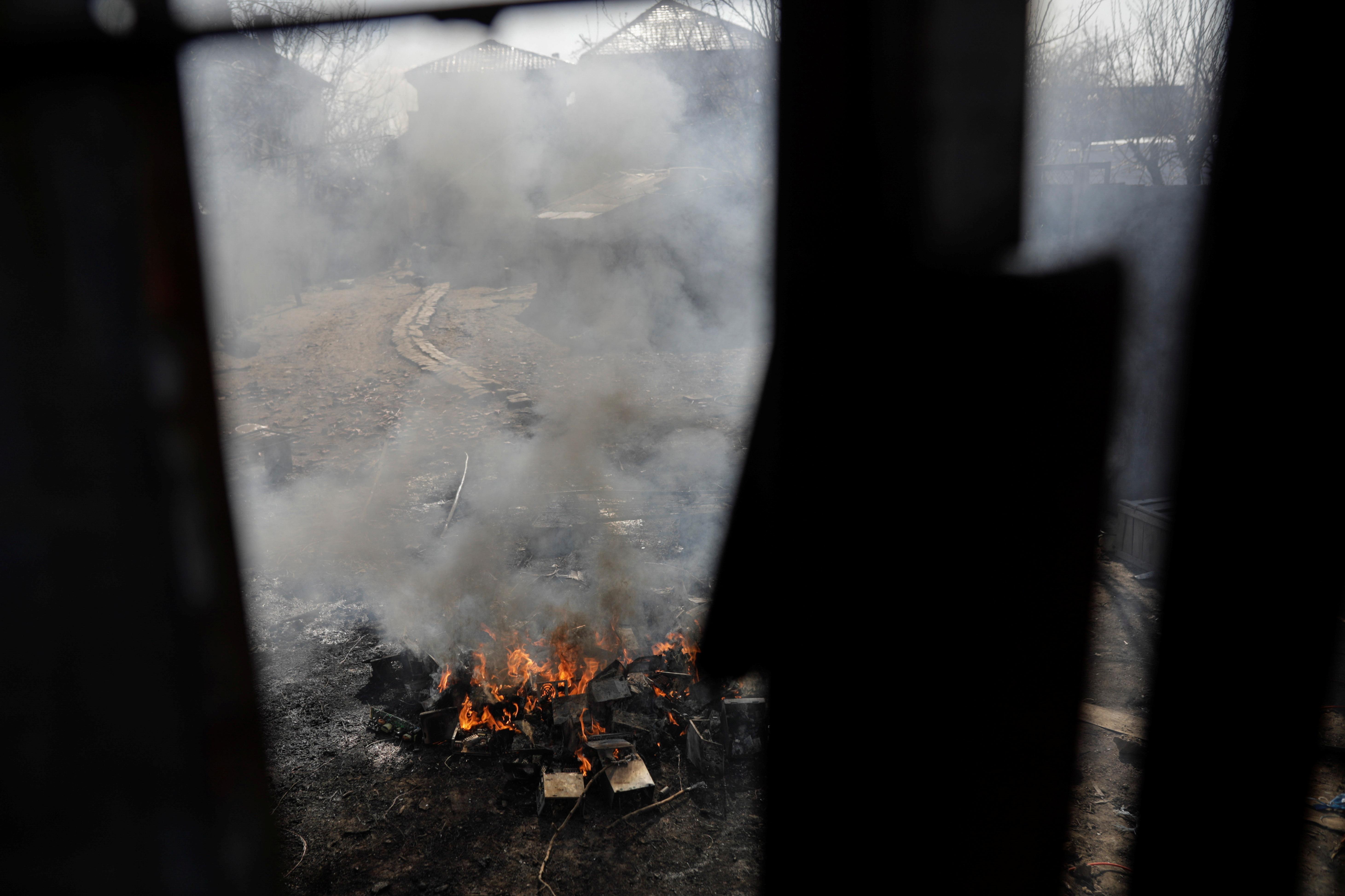 Dismantled electronics burn in a courtyard in Sintesti village, Ilfov, Romania, April 9, 2021. Inquam Photos/George Calin via REUTERS