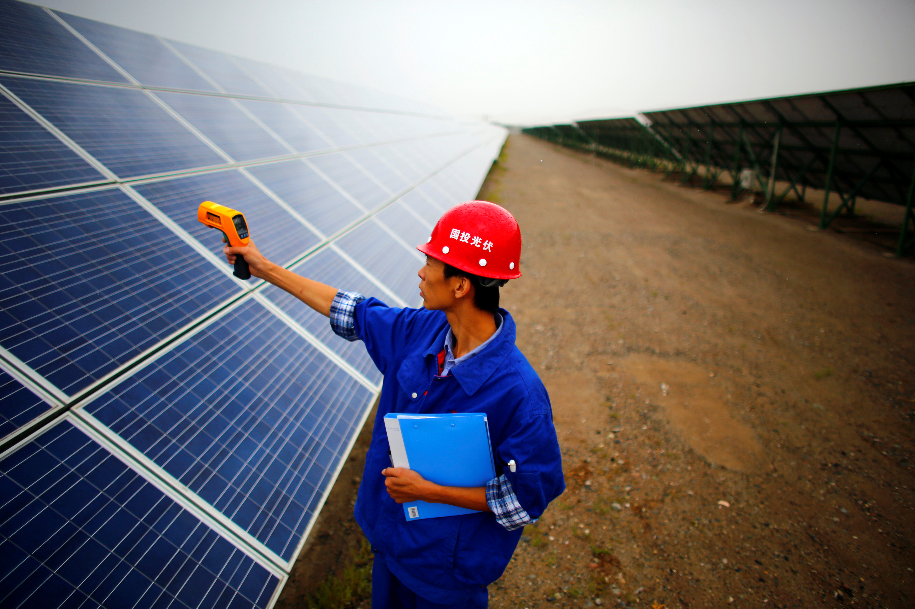 A worker inspects solar panels at a solar farm in Dunhuang, 950km (590 miles) northwest of Lanzhou, Gansu Province September 16, 2013. REUTERS/Carlos Barria/File Photo