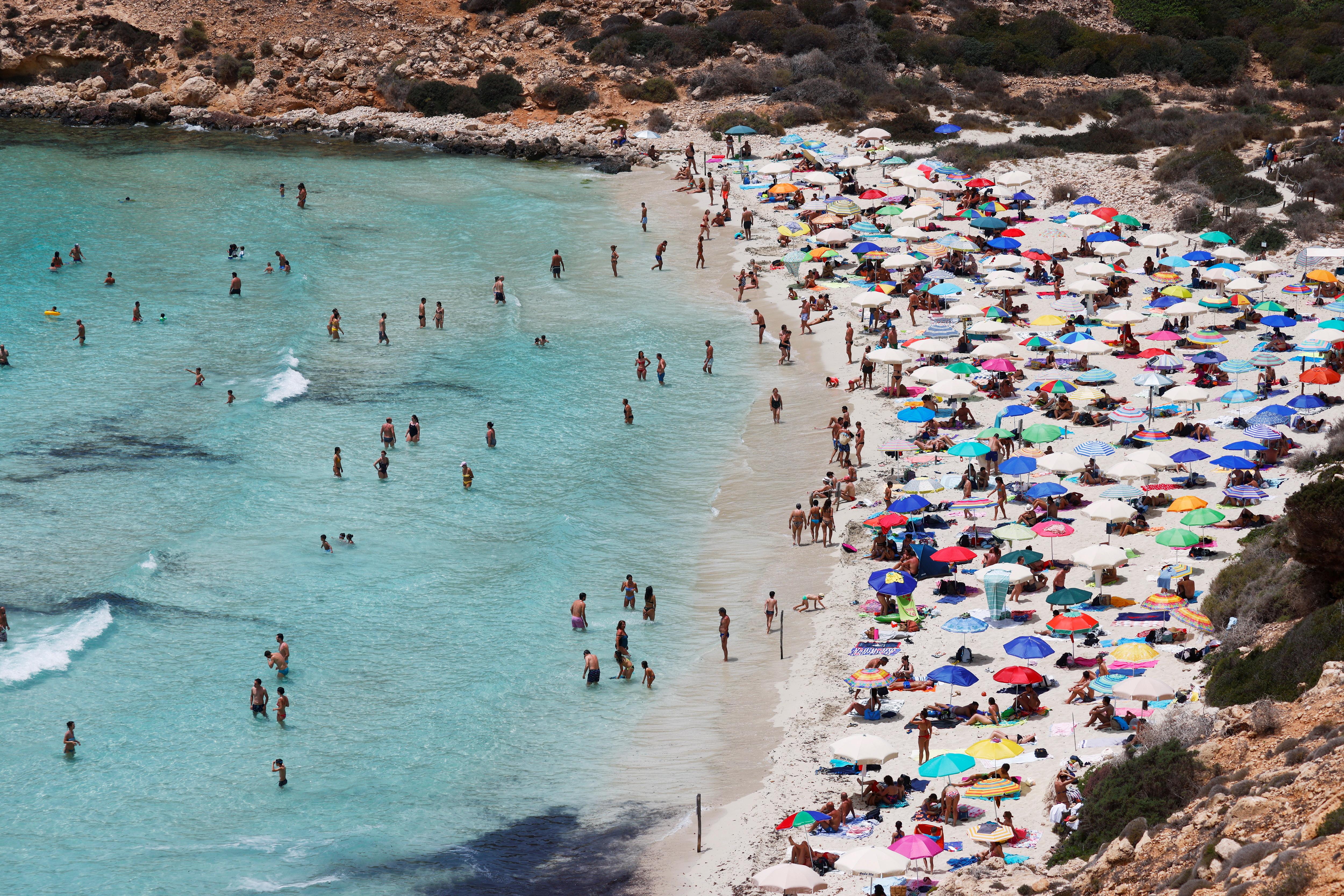 People sunbathe on the beach on the Sicilian island of Lampedusa, as a flow of migrants arriving on the Mediterranean island, in Lampedusa, Italy, June 22, 2021. REUTERS/Guglielmo Mangiapane