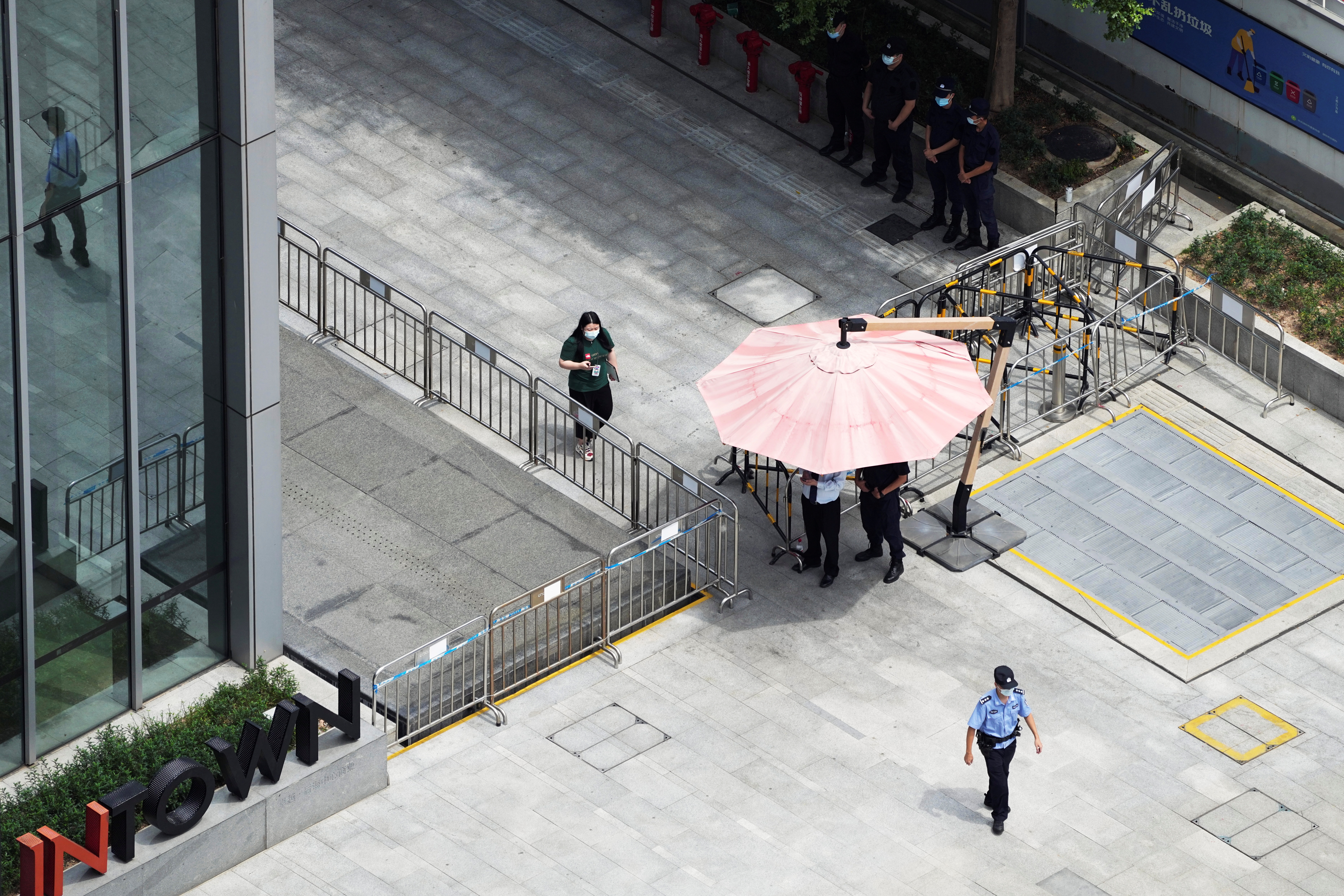 Police and security personnel keep watch outside the headquarters of China Evergrande Group in Shenzhen, Guangdong province, China September 26, 2021. REUTERS/Aly Song