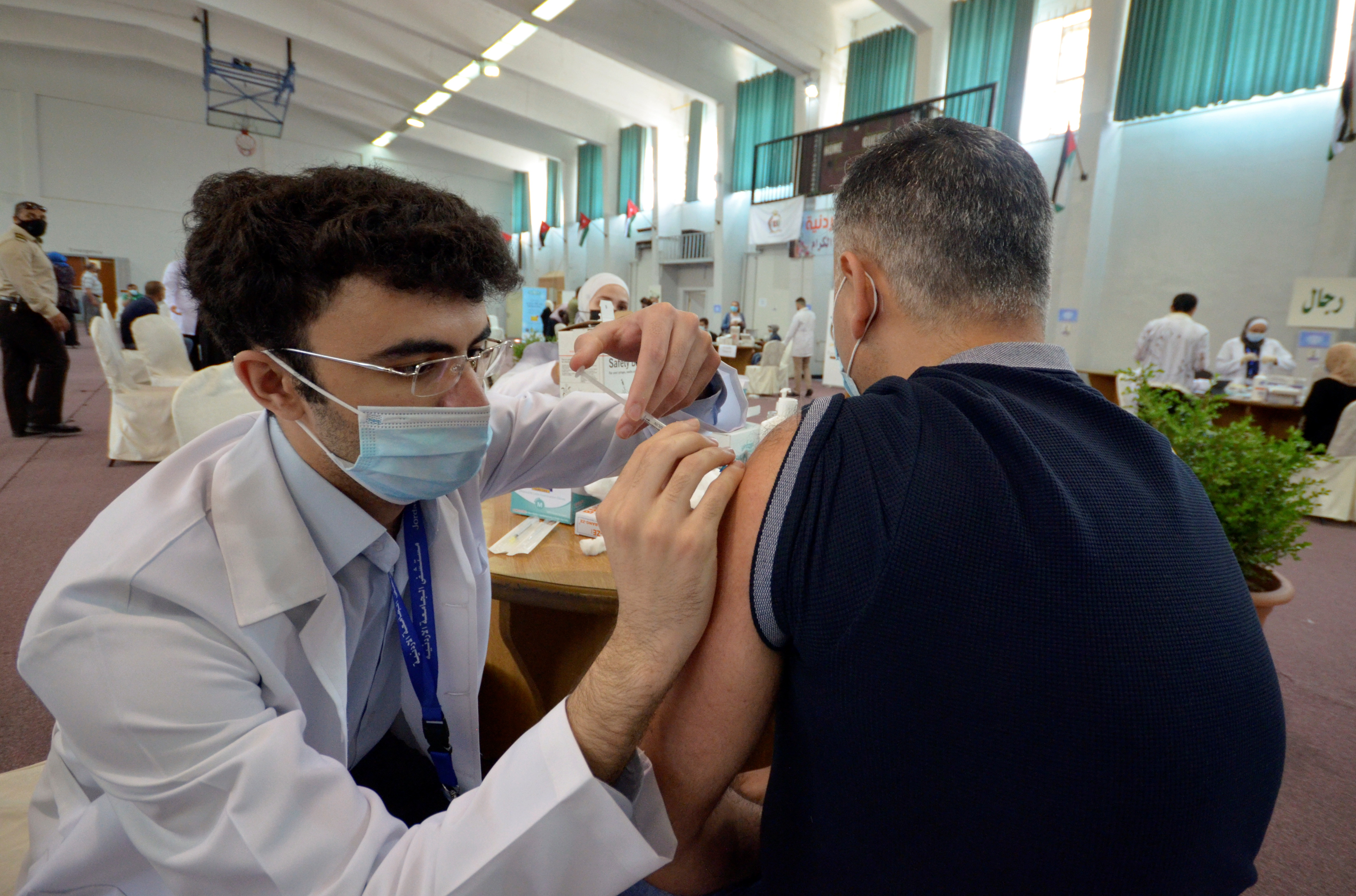 A medical worker administers the coronavirus disease (COVID-19) vaccine to a man in Amman, Jordan, May 3, 2021. Picture taken May 3, 2021. REUTERS/Muath Freij/Files