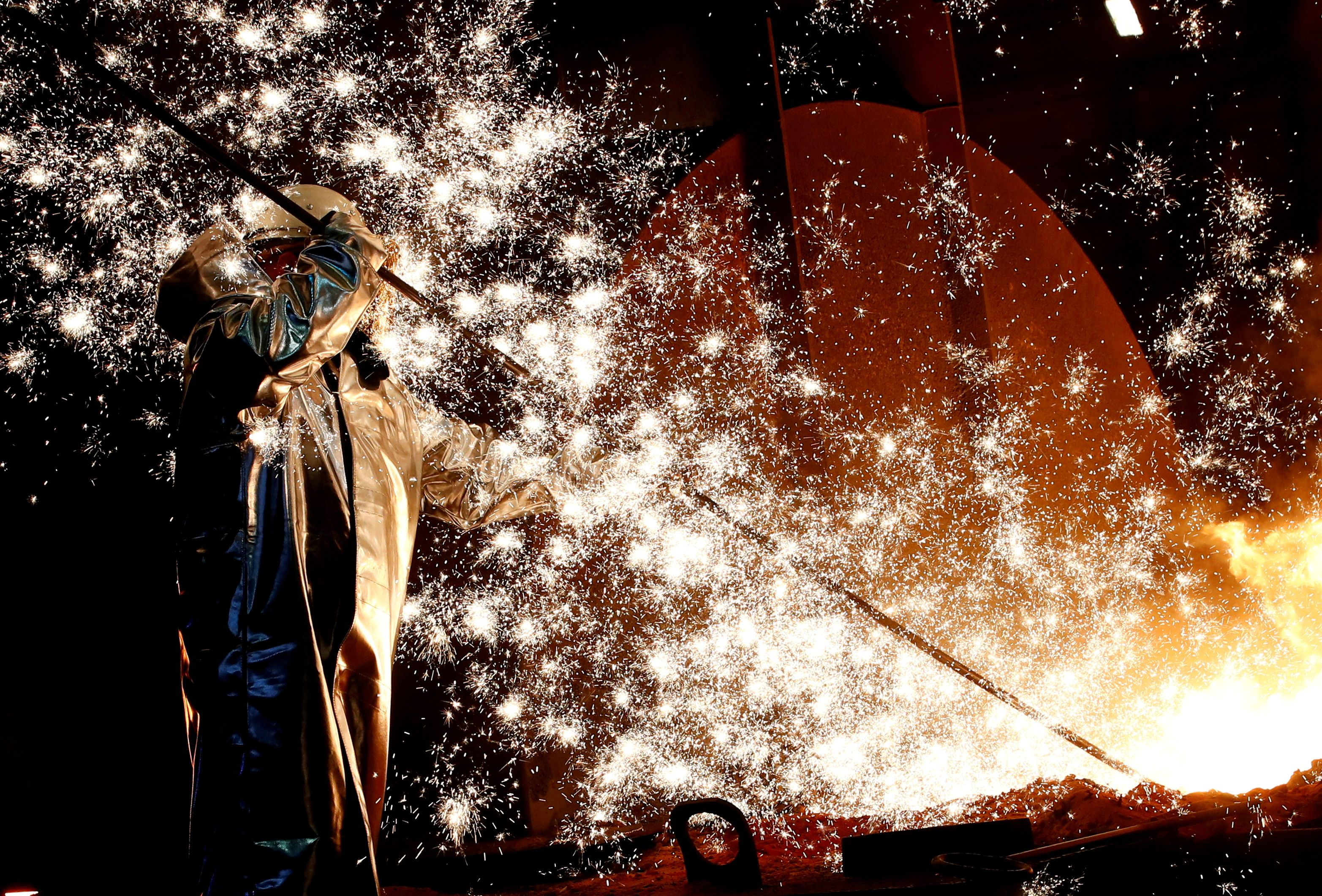 A steel worker of Germany's industrial conglomerate ThyssenKrupp AG stands a mid of emitting sparks of raw iron from a blast furnace at Germany's largest steel factory in Duisburg, Germany. REUTERS/Wolfgang Rattay