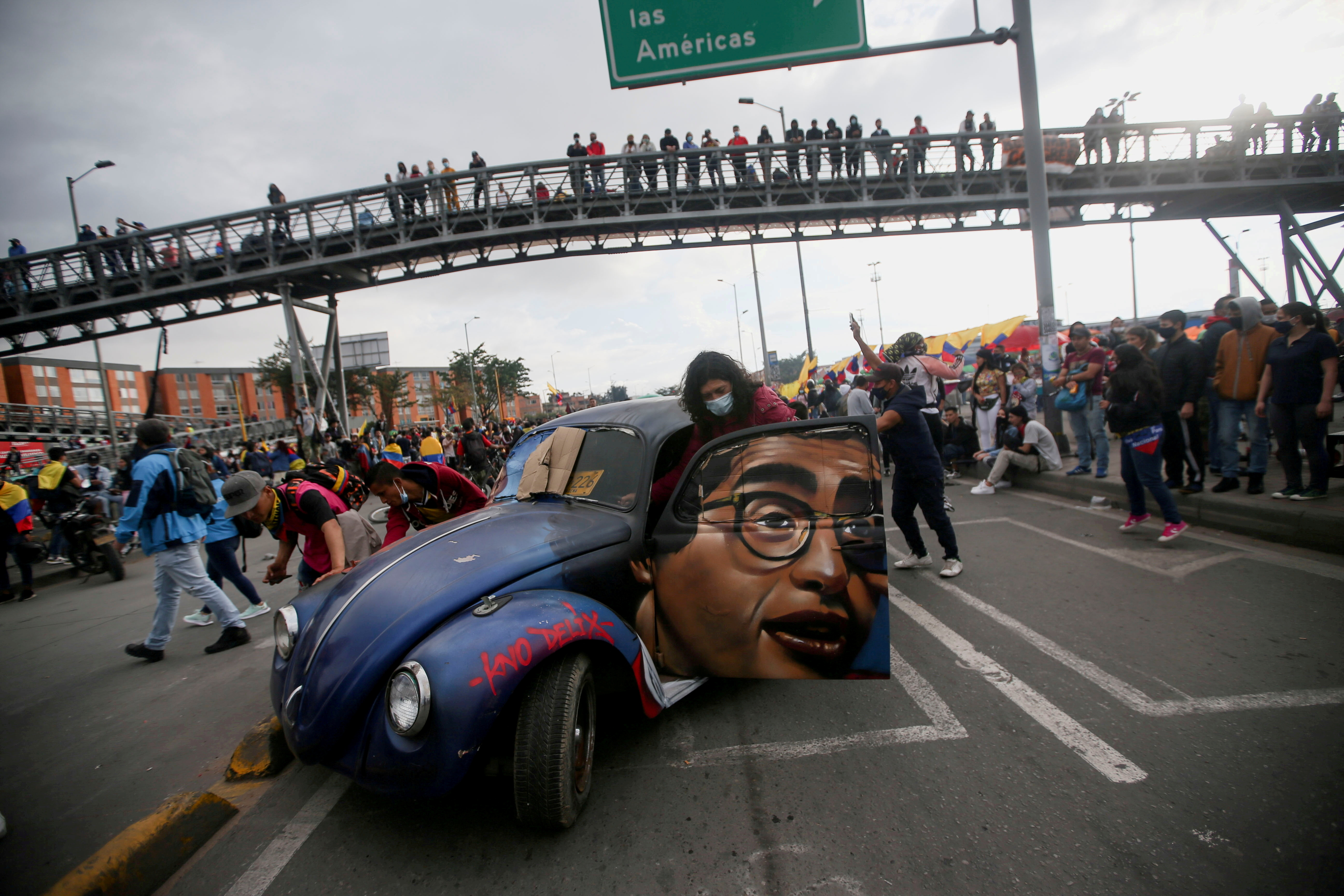 People push a car with the image of late Colombian humorist and journalist Jaime Garzon painted on it during a protest demanding government action to tackle poverty, police violence and inequalities in healthcare and education systems, in Bogota, Colombia,  June 2, 2021. REUTERS/Luisa Gonzalez/File Photo