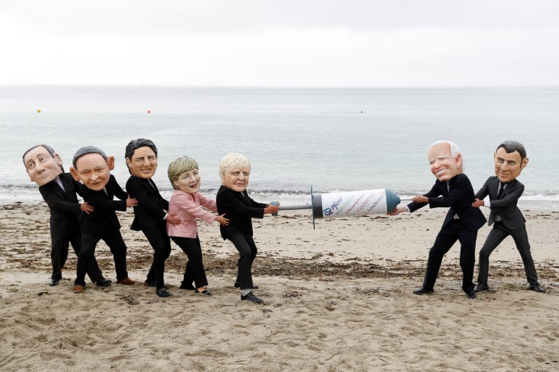 Oxfam activists with 'Big Heads' caricatures of U.S. President Joe Biden and France's President Emmanuel Macron pretend to fight over a COVID-19 vaccine with other G7 leaders, during a protest at a beach near Falmouth, on the sidelines of G7 summit, in Cornwall, Britain, June 11, 2021.  REUTERS/Peter Nicholls