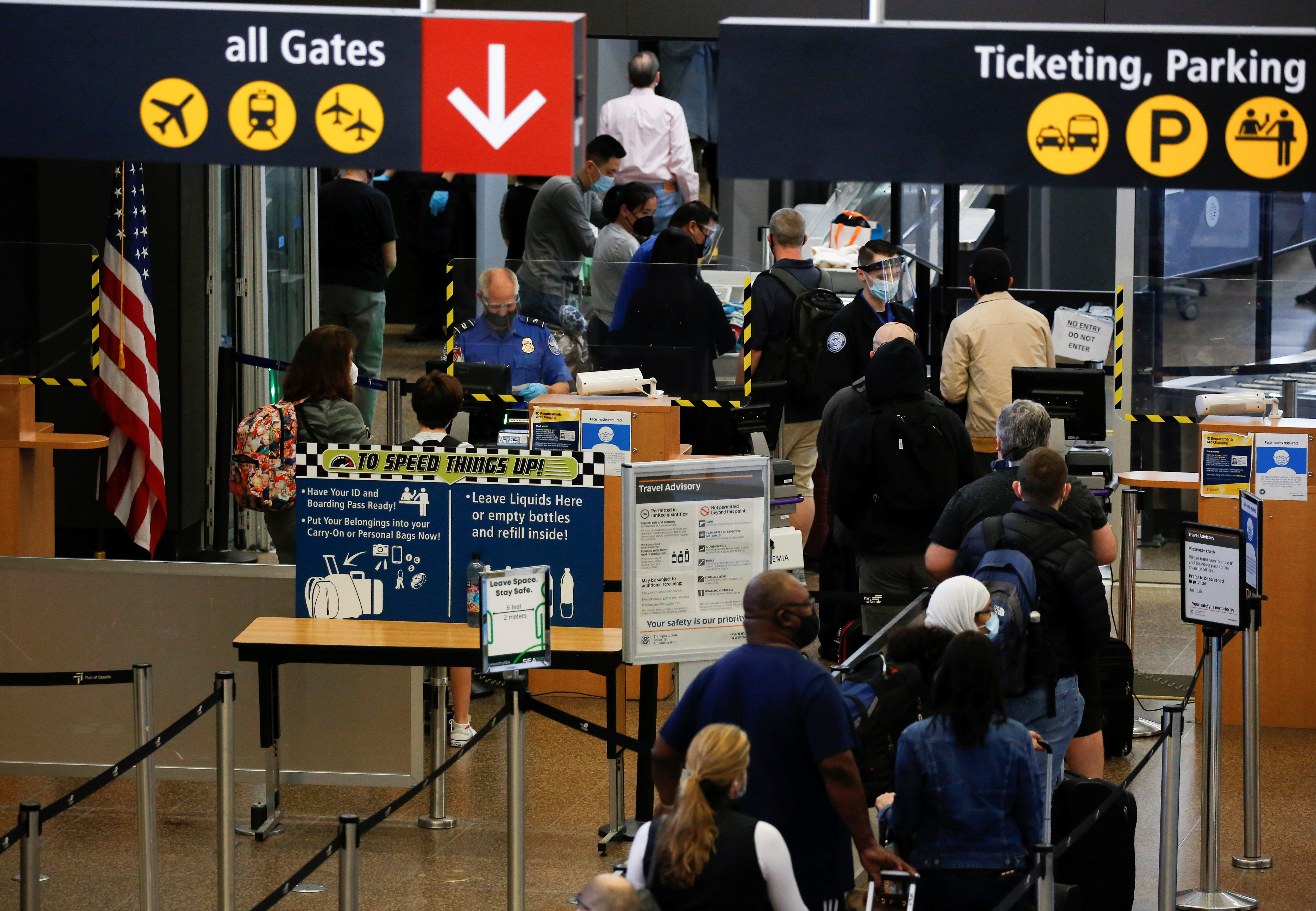 Travelers queue in a security line limited to every other lane for social distancing at Seattle-Tacoma International Airport in SeaTac, Washington, U.S. April 12, 2021.  REUTERS/Lindsey Wasson