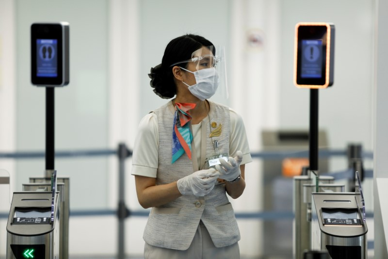 An airport staff member wearing a protective face mask and shield, amid the coronavirus disease (COVID-19) pandemic, stands at the Haneda airport in Tokyo, Japan June 13, 2021. REUTERS/Androniki Christodoulou/File Photo