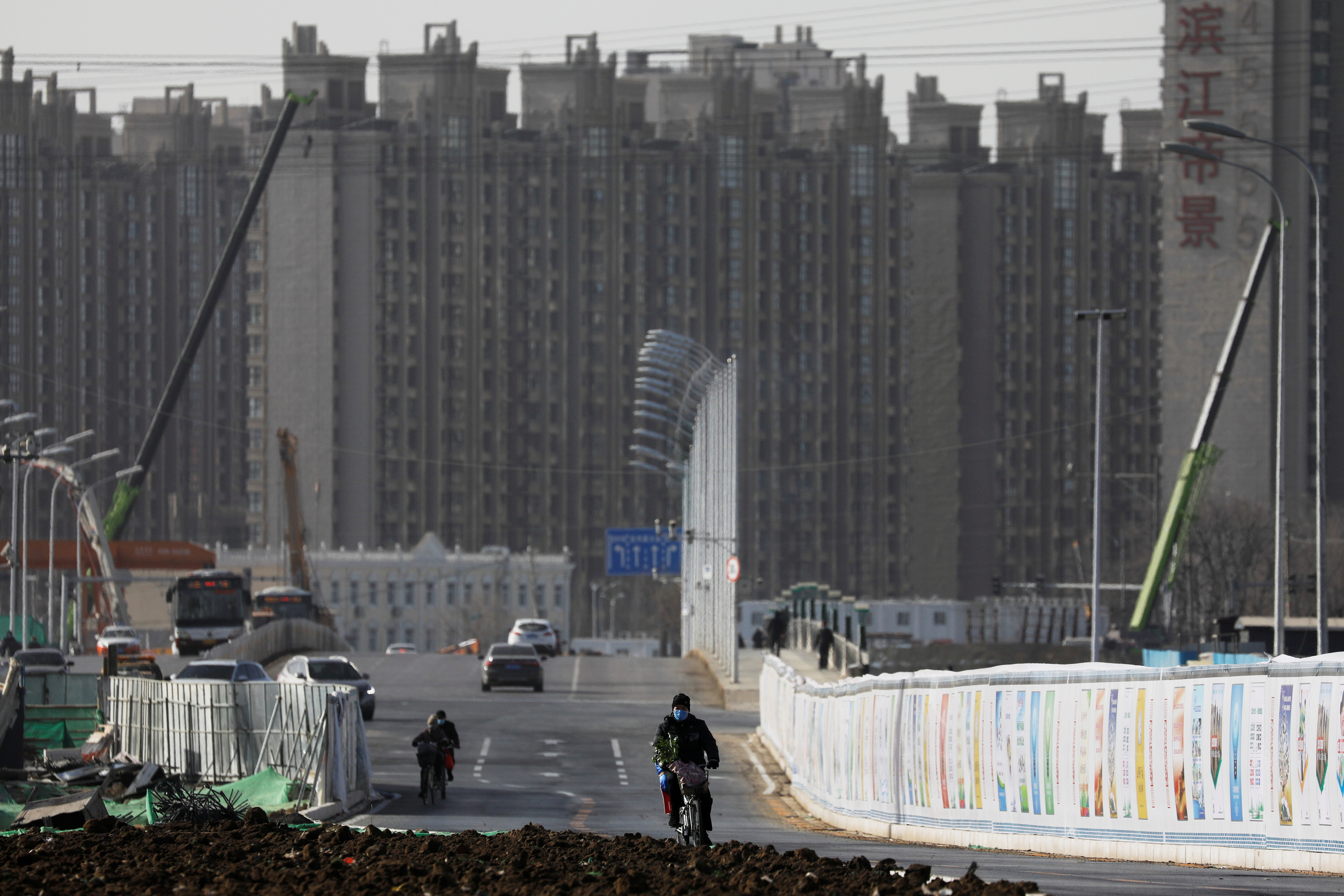 A man rides a bicycle next to a construction site near residential buildings in Beijing, China, January 13, 2021.  REUTERS/Tingshu Wang/File Photo