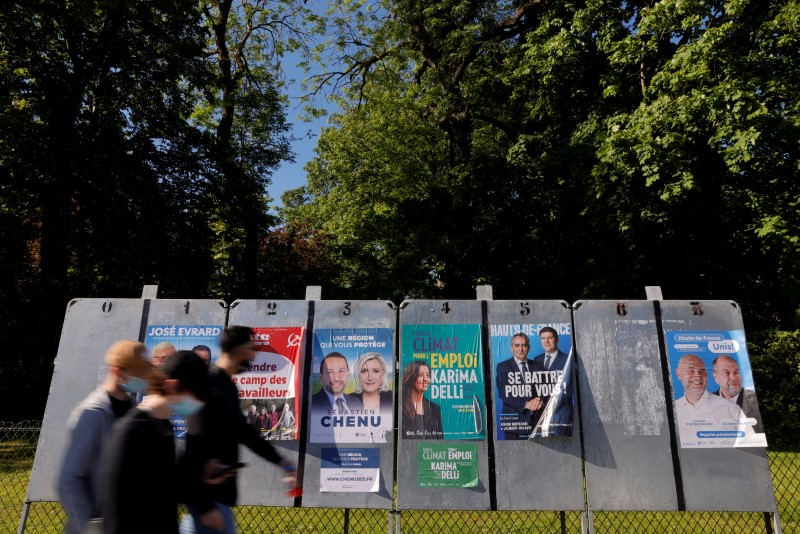 People, wearing a protective face mask, walk past electoral panels ahead of the upcoming French regional elections in Cambrai, France, June 1, 2021. REUTERS/Pascal Rossignol/File Photo