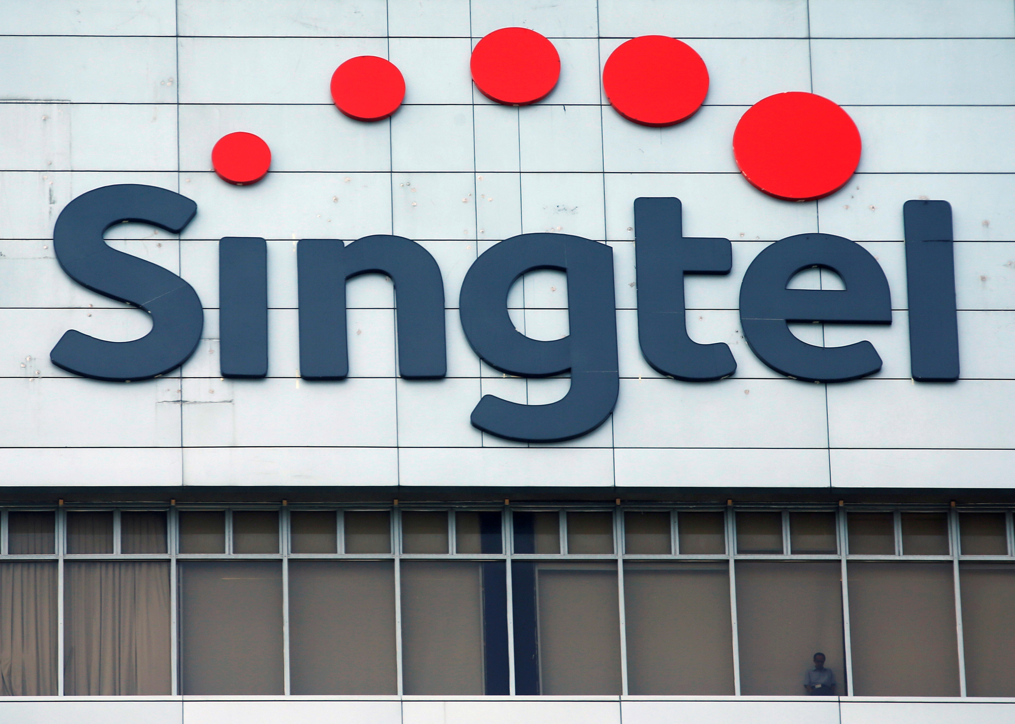 A man looks out of the window under a Singtel signage at their head office in Singapore February 12, 2015.  REUTERS/Edgar Su