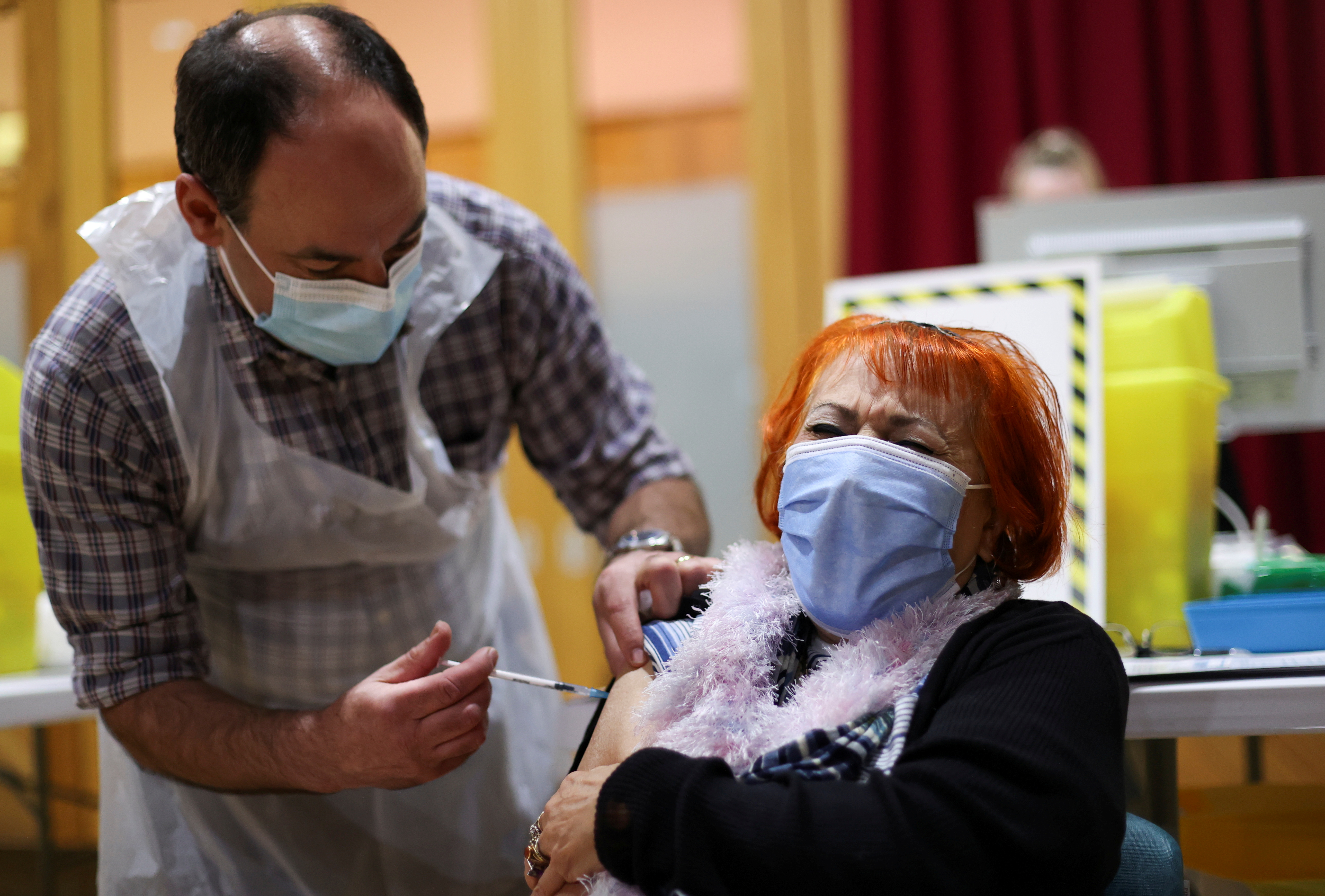 A woman receives a vaccine against the coronavirus disease (COVID-19) in the Winding Wheel Theatre, Chesterfield, Britain February 3, 2021. REUTERS/Carl Recine