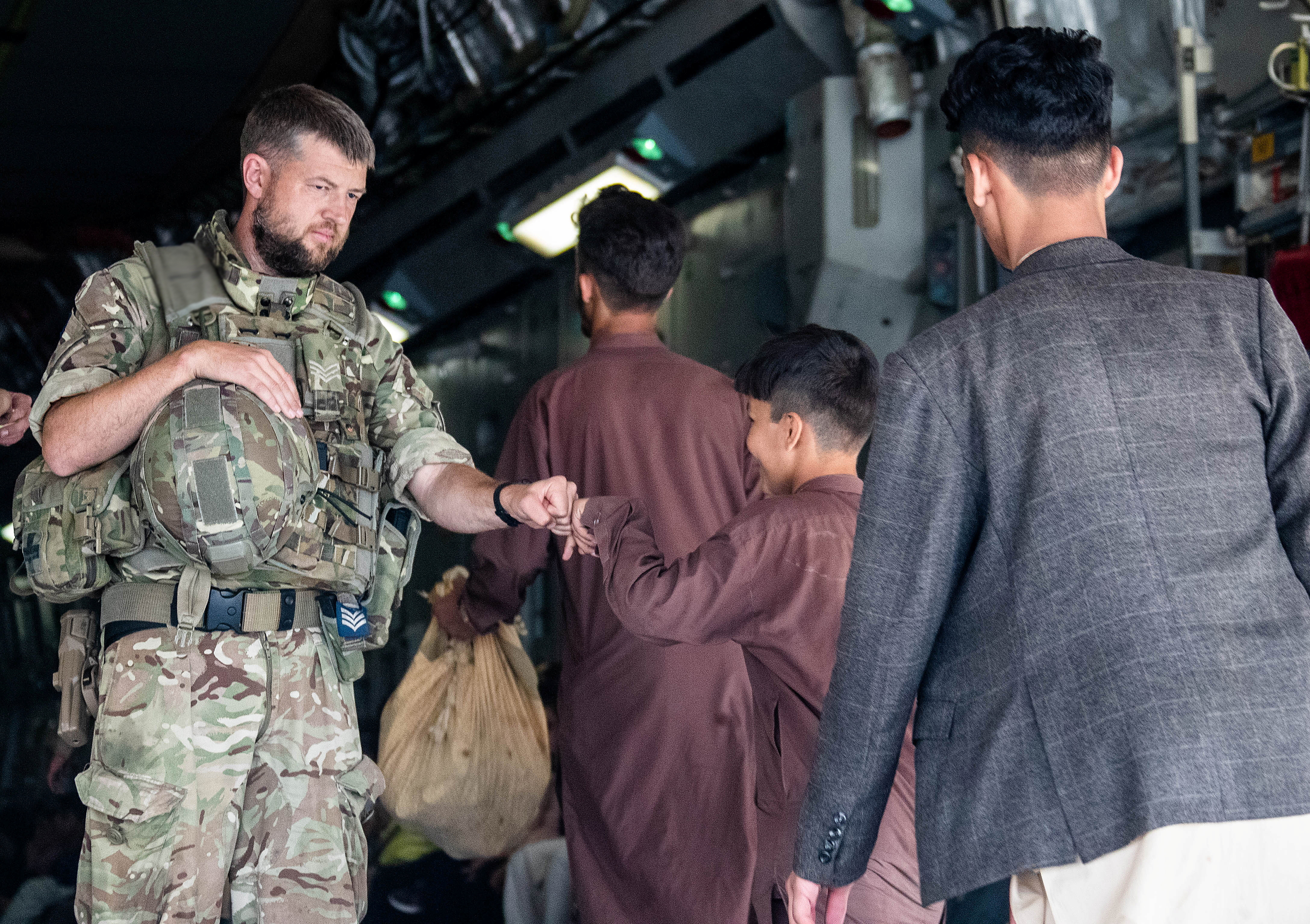A member of the UK Armed Forces bumps fists with a child as he continues to take part in the evacuation of entitled personnel from Kabul airport, in Kabul, Afghanistan August 19-22, 2021, in this handout picture obtained by Reuters on August 23, 2021. LPhot Ben Shread/UK MOD Crown copyright 2021/Handout via REUTERS/Files