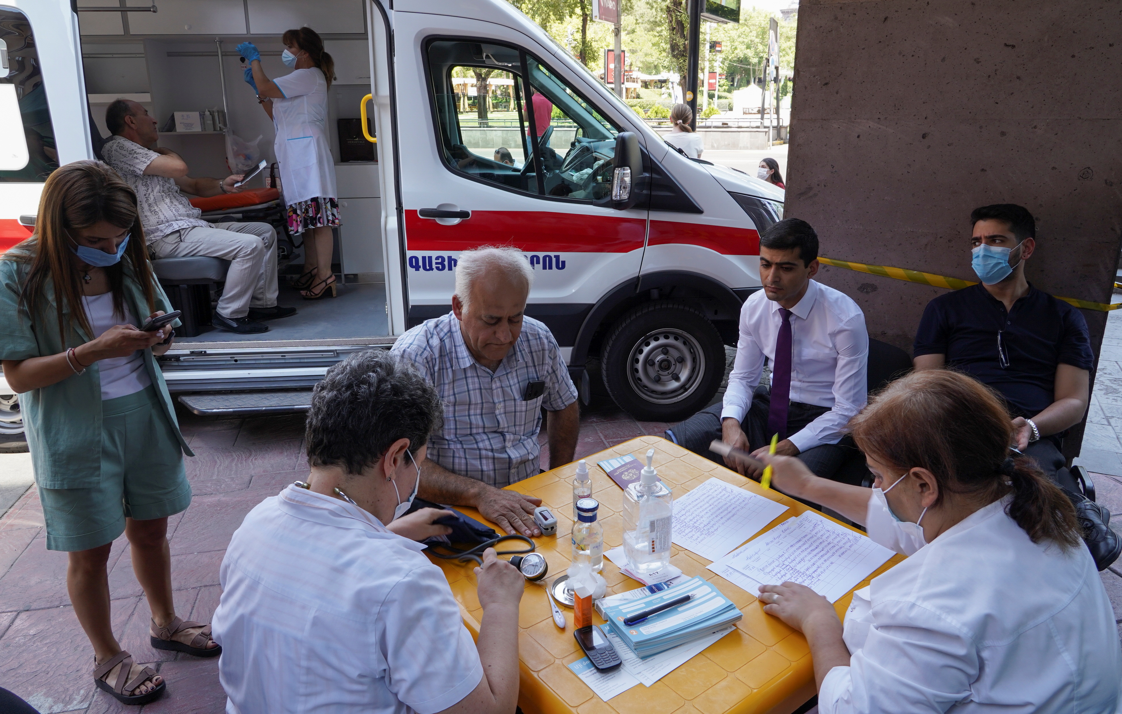 Iranian citizens prepare to get vaccinated with AstraZeneca vaccine against the coronavirus disease (COVID-19) at a mobile vaccination centre in Yerevan, Armenia July 19, 2021.  REUTERS/Artem Mikryukov