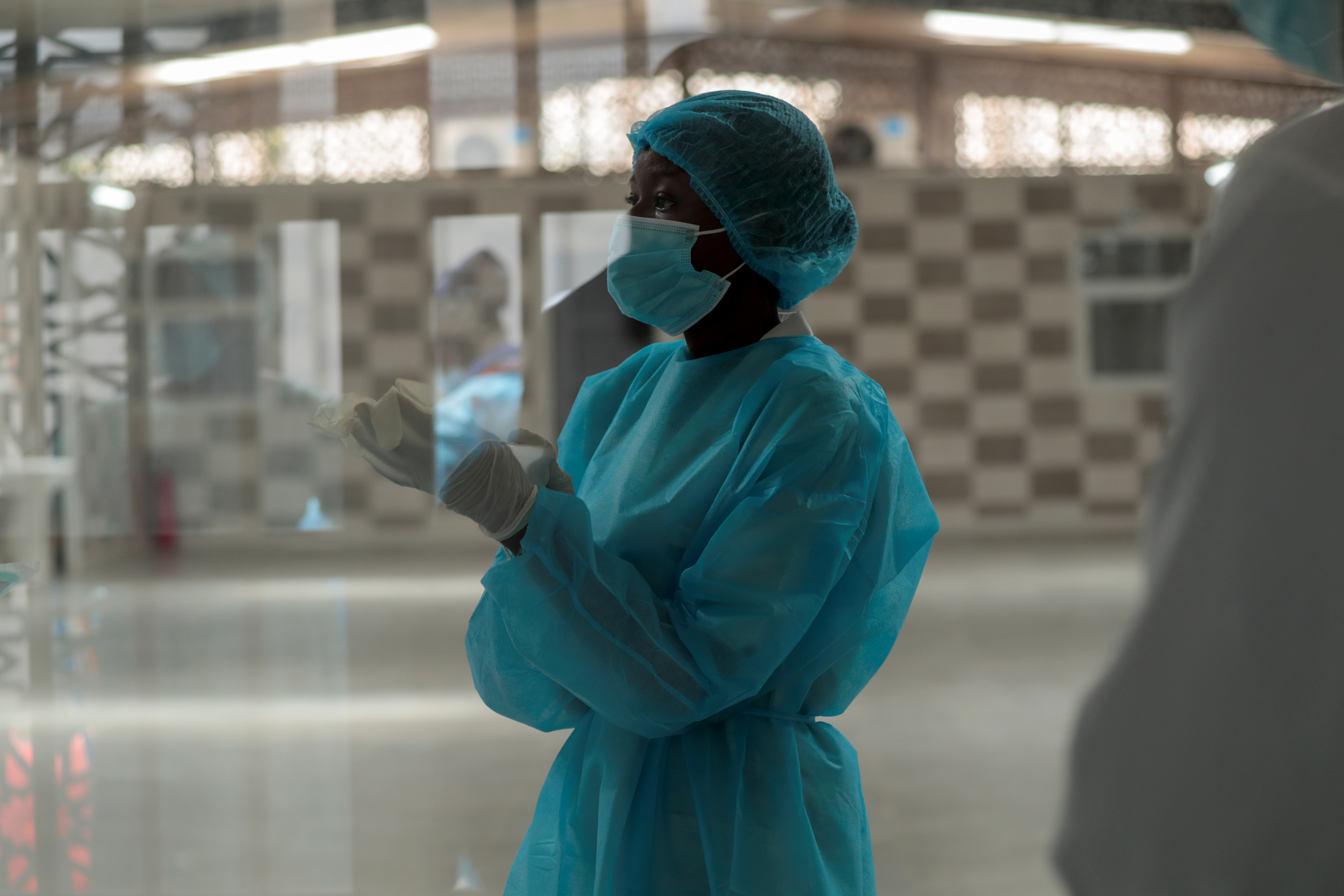 A health worker is pictured through a window at the infectious diseases department of the Fann University Hospital in Dakar, amid a surge of coronavirus disease (COVID-19) cases in Senegal July 28, 2021. REUTERS/Zohra Bensemra