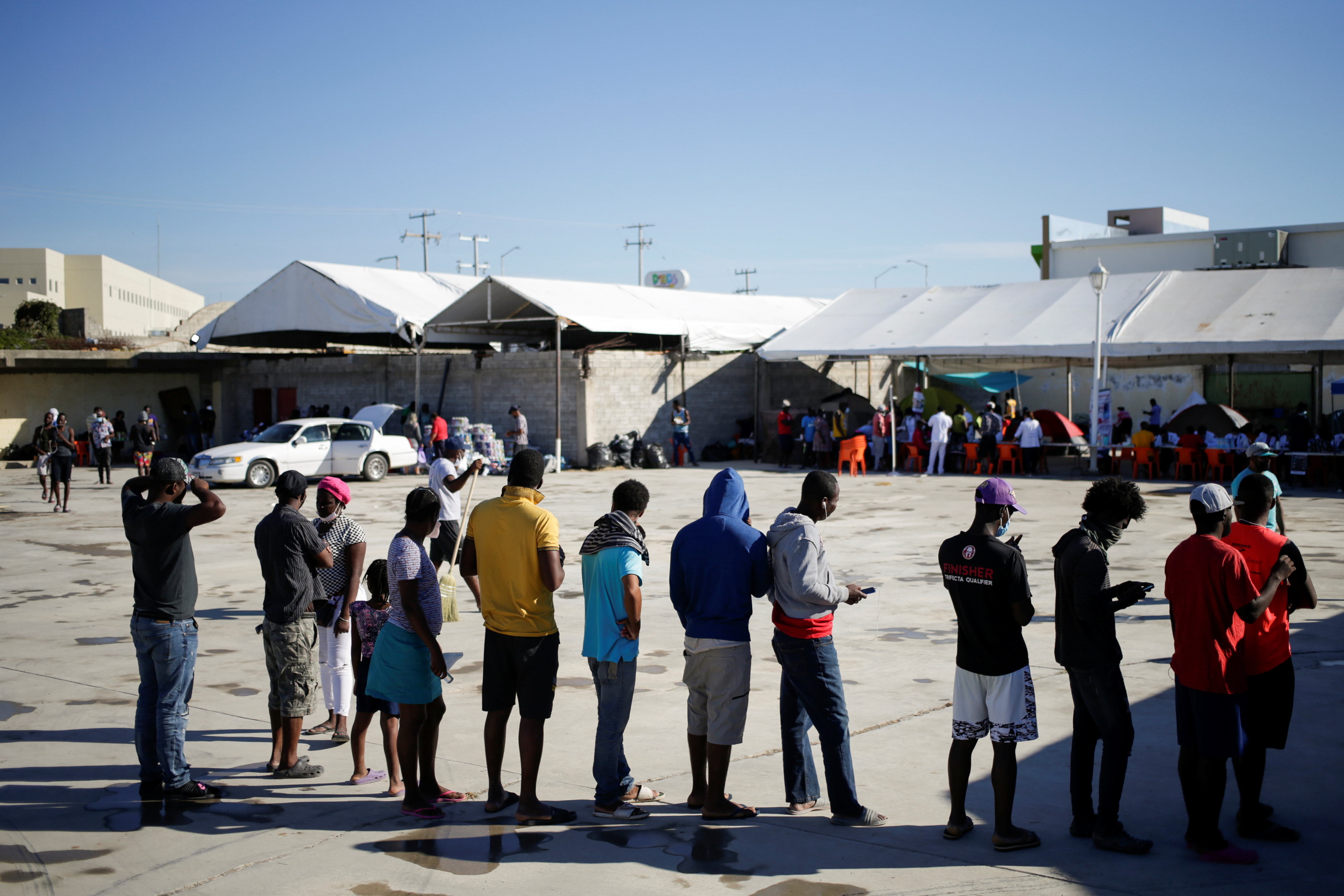 Migrants from Haiti, who returned to the Mexican side of the border to avoid deportation, queue for breakfast at a shelter set by the National Migration Institute (INM) in Ciudad Acuna, Mexico, September 25, 2021. REUTERS/Daniel Becerril