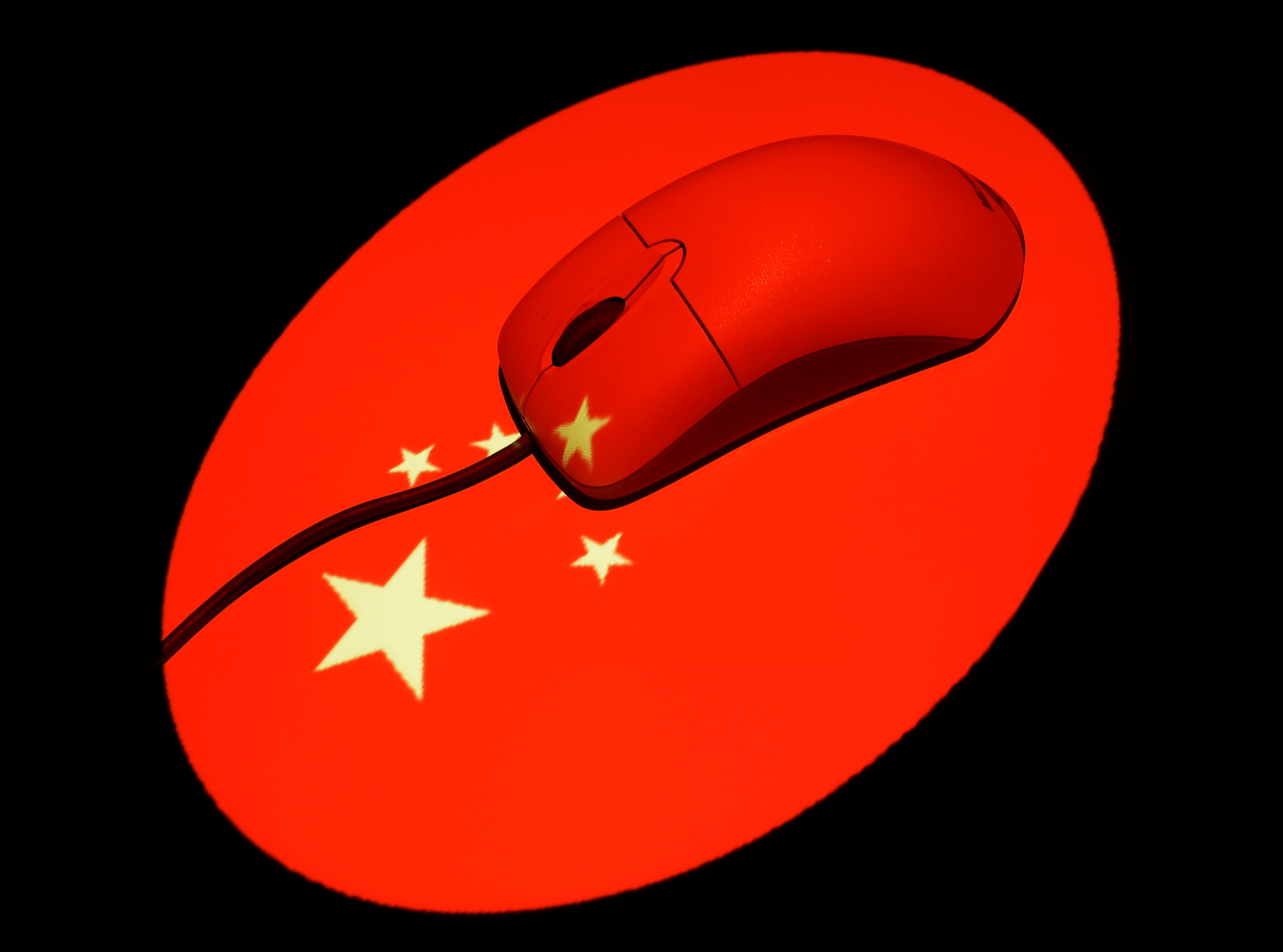 A computer mouse is illuminated by a projection of a Chinese flag in this photo illustration October 1, 2013. REUTERS/Tim Wimborne/File Photo