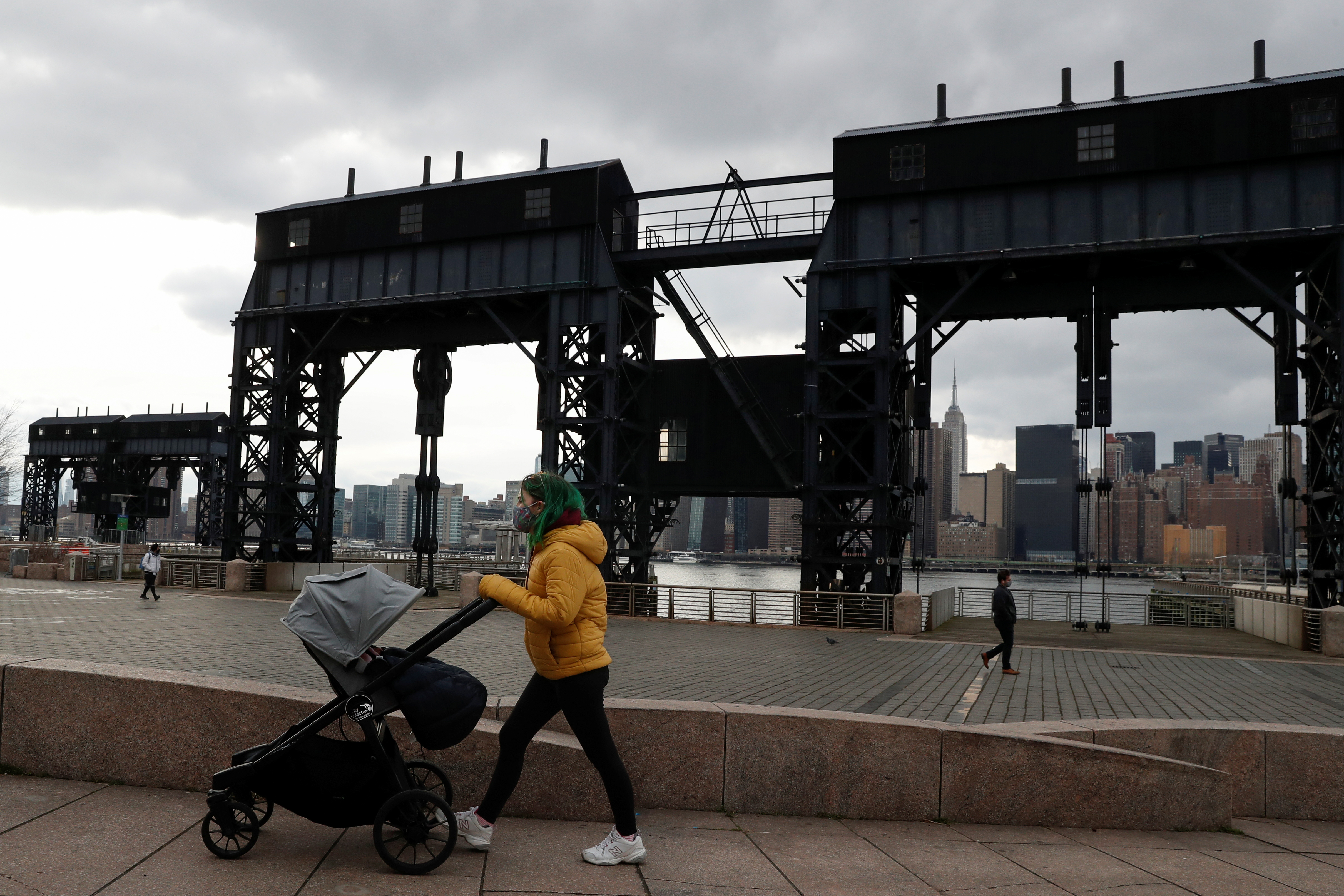 A woman wearing a protective face mask pushes a baby stroller, amid the spread of the coronavirus disease (COVID-19), at Gentry Plaza State Park in the Queens borough of New York, U.S., March 1, 2021. REUTERS/Shannon Stapleton