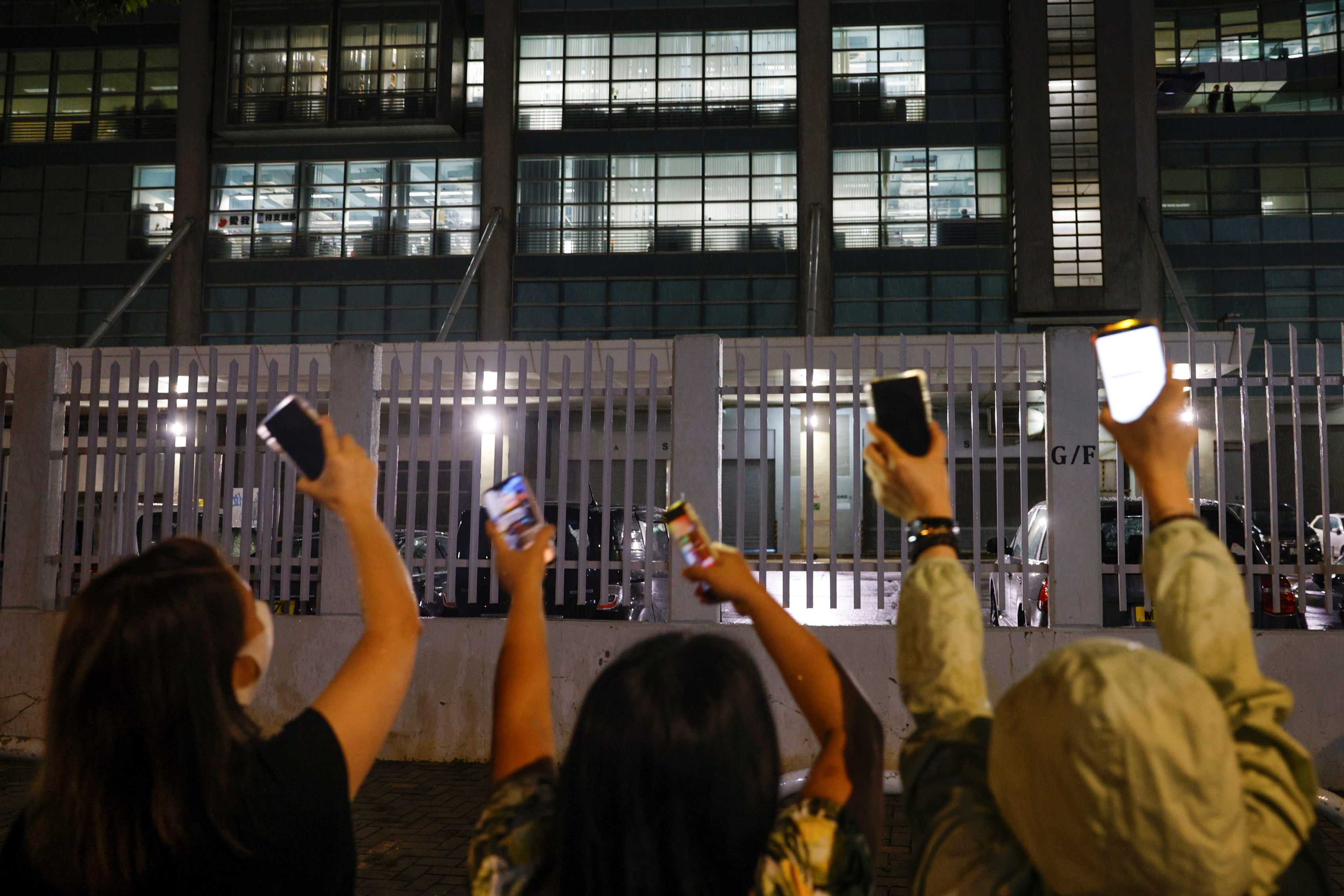 Supporters light torch lights from their phones outside the headquarters of the Apple Daily newspaper, and its publisher Next Digital, after announcement that the newspaper is folding its operations earlier, in Hong Kong, China June 23, 2021. REUTERS/Tyrone Siu