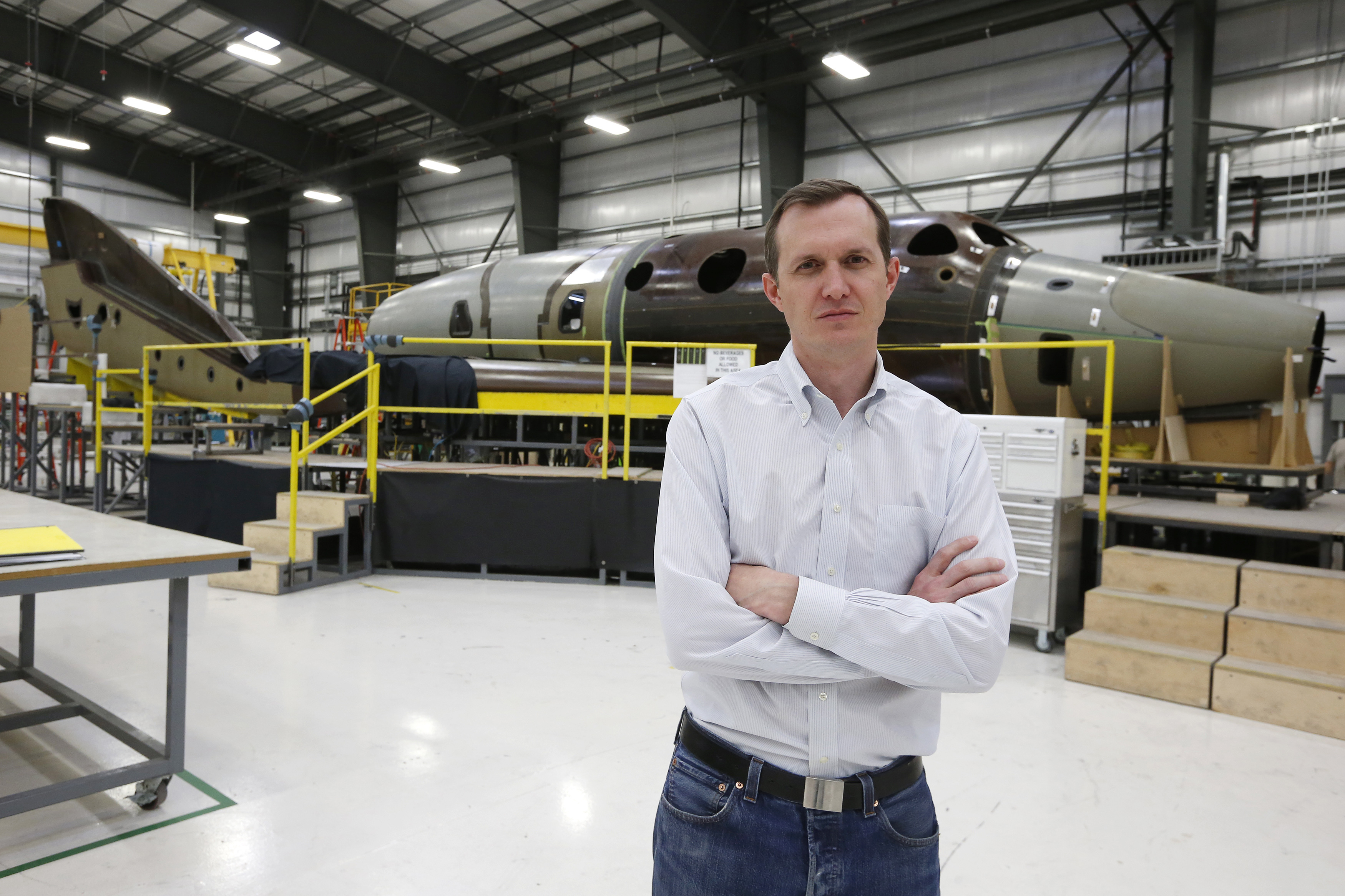 Virgin Galactic's CEO George T. Whitesides stands in front of their new spaceship N202VG, which the company began building 2 and a half years ago, in a hangar at Mojave Air and Space Port in Mojave, California November 4, 2014. REUTERS/Lucy Nicholson