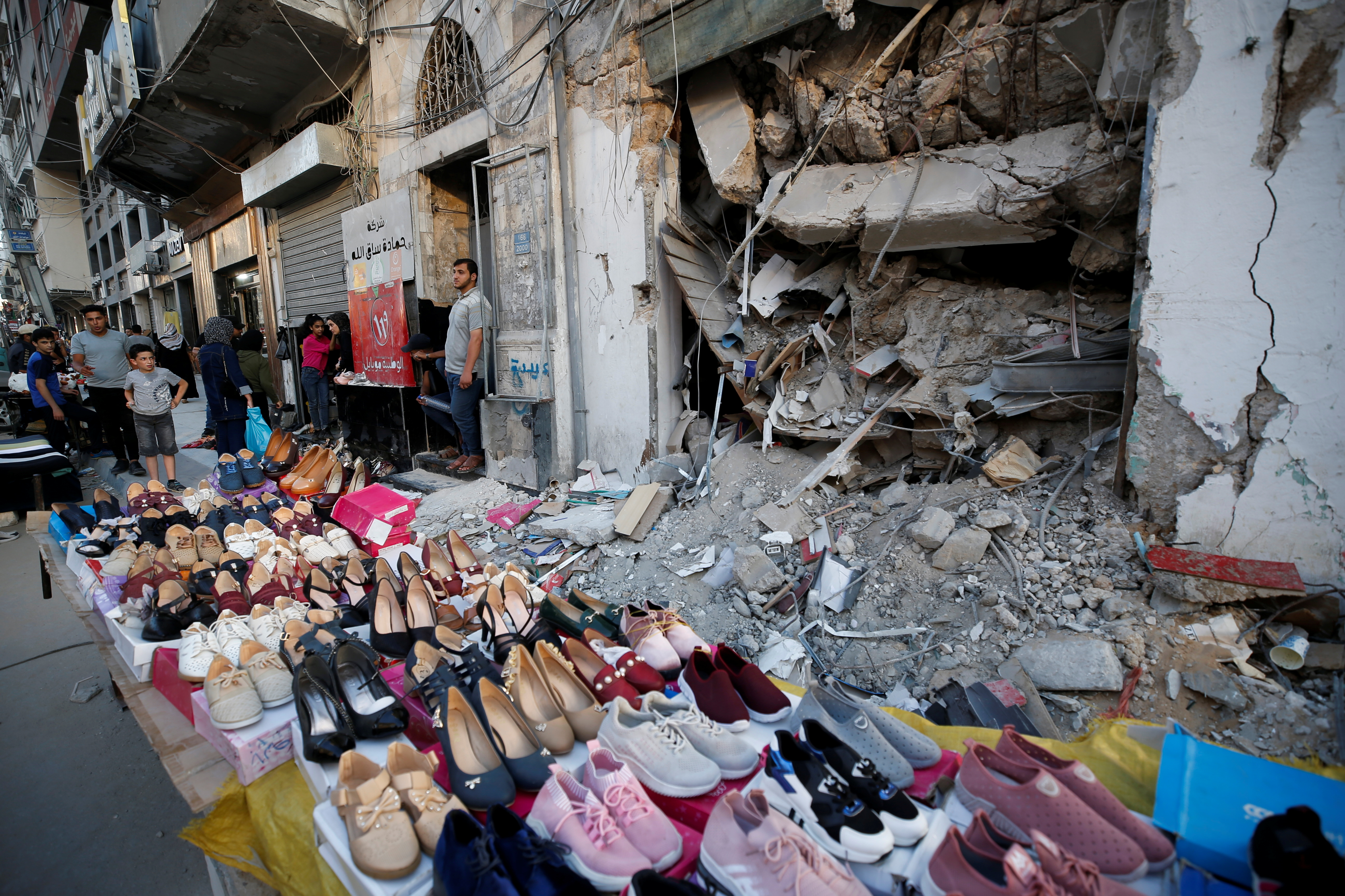 A Palestinian sells shoes on a stall near the rubble of his old shoe store that has been destroyed in an Israeli air strike, ahead of Eid Al-Adha Muslim holiday, in Gaza City, July 14, 2021. Picture taken July 14, 2021. REUTERS/Mohammed Salem