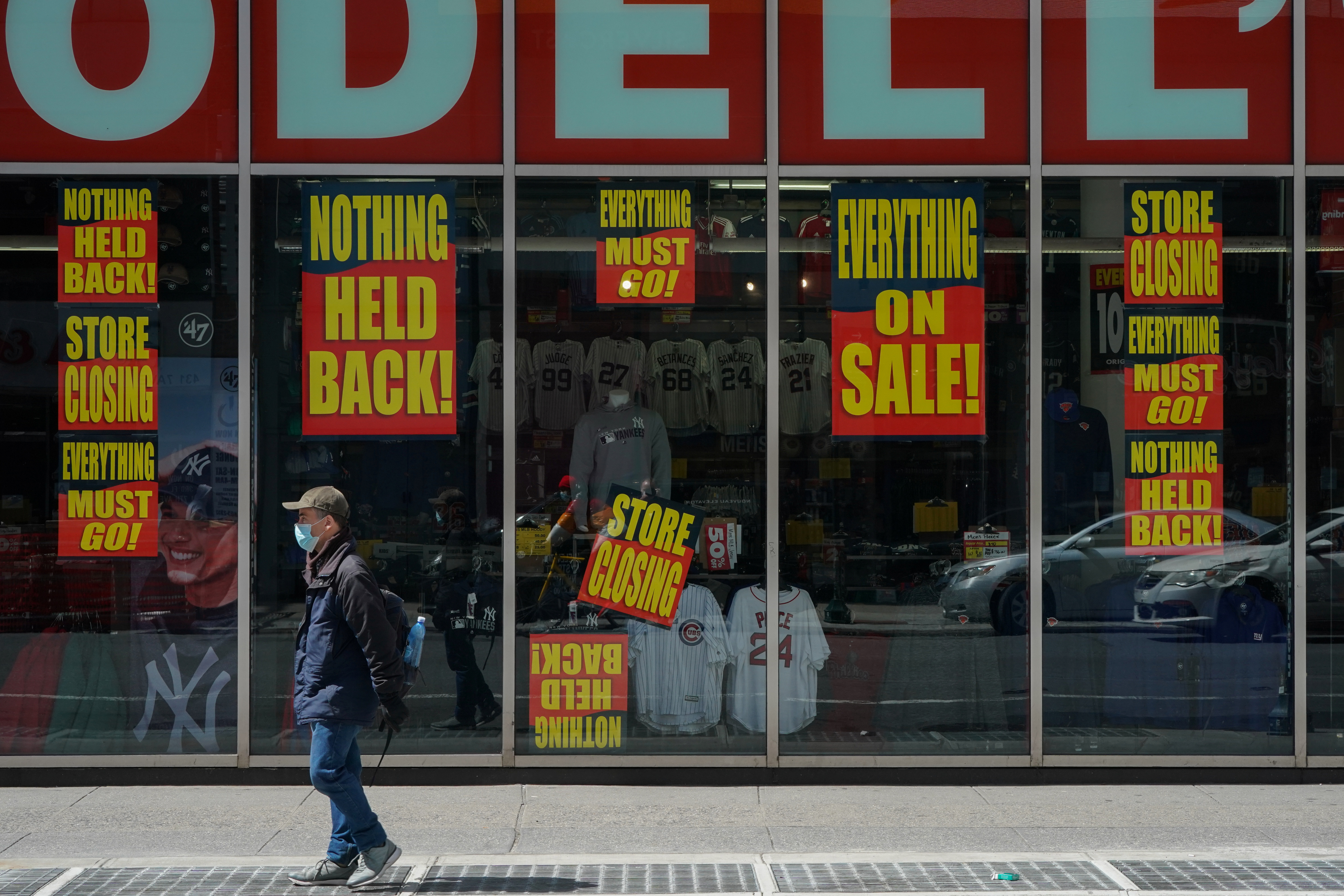 A man stands in front of a Modell's store that is closed as retail sales suffer record drop during the outbreak of the coronavirus disease (COVID-19) in New York City, New York, U.S., April 15, 2020. REUTERS/Bryan R Smith