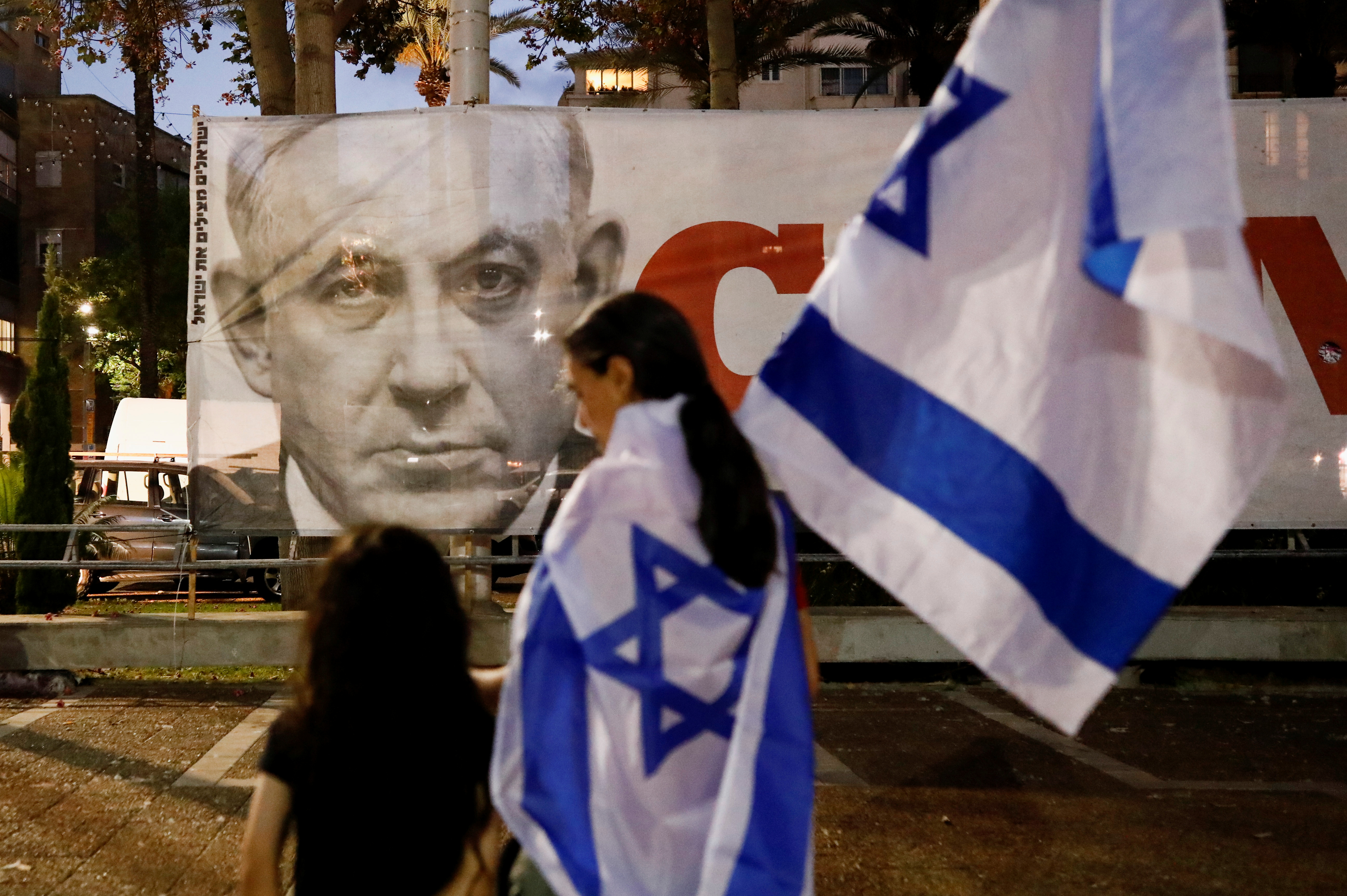 People walk in front of a picture of former Prime Minister Benjamin Netanyahu after Israel's parliament voted in a new coalition government, ending Netanyahu's 12-year hold on power, in Tel Aviv, Israel June 13, 2021. REUTERS/Corinna Kern
